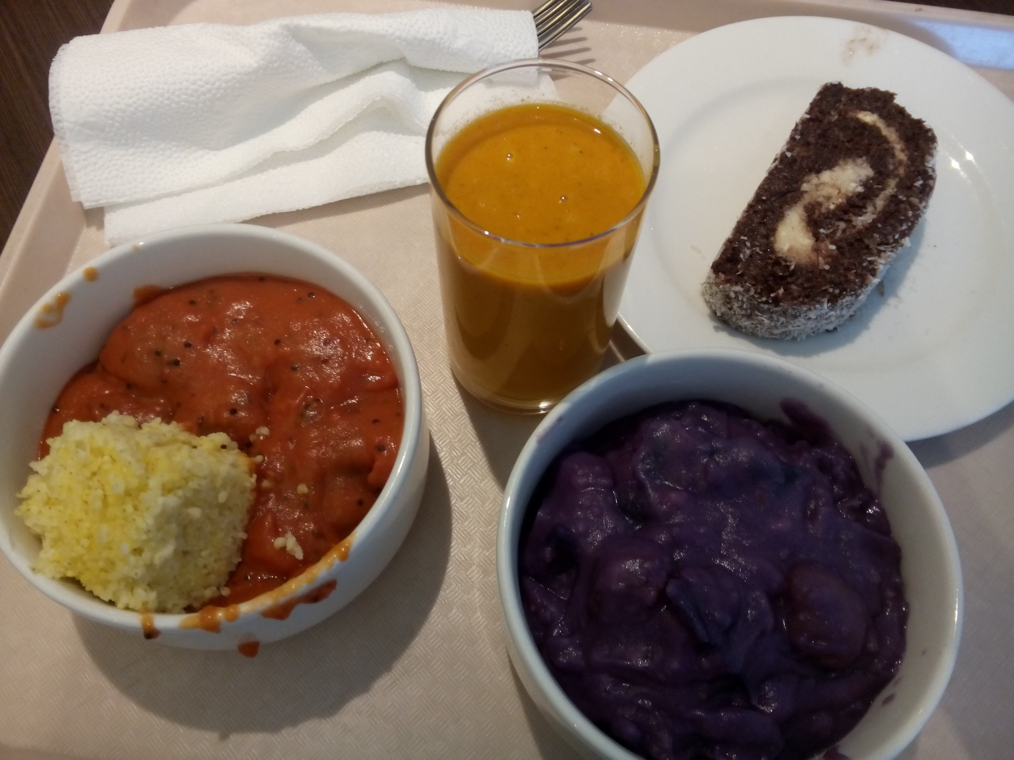 Two bowls, one containing red mush and millet, one with dark purple mush; in between an orange smoothie, and beside a swirly slice of cake