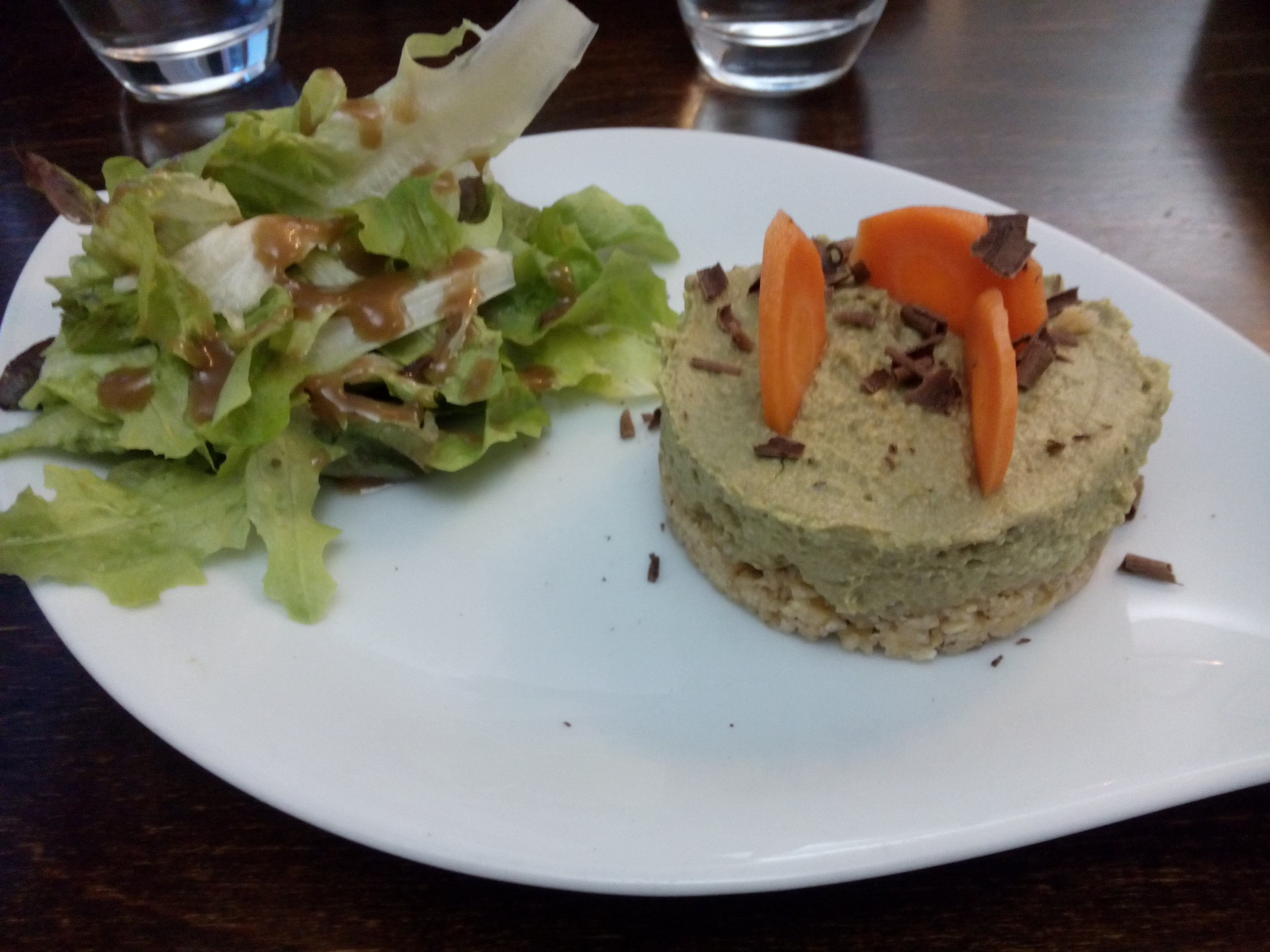 A white plate with salad on left and a round stack of avocado with some carrot and chocolate shreds on top