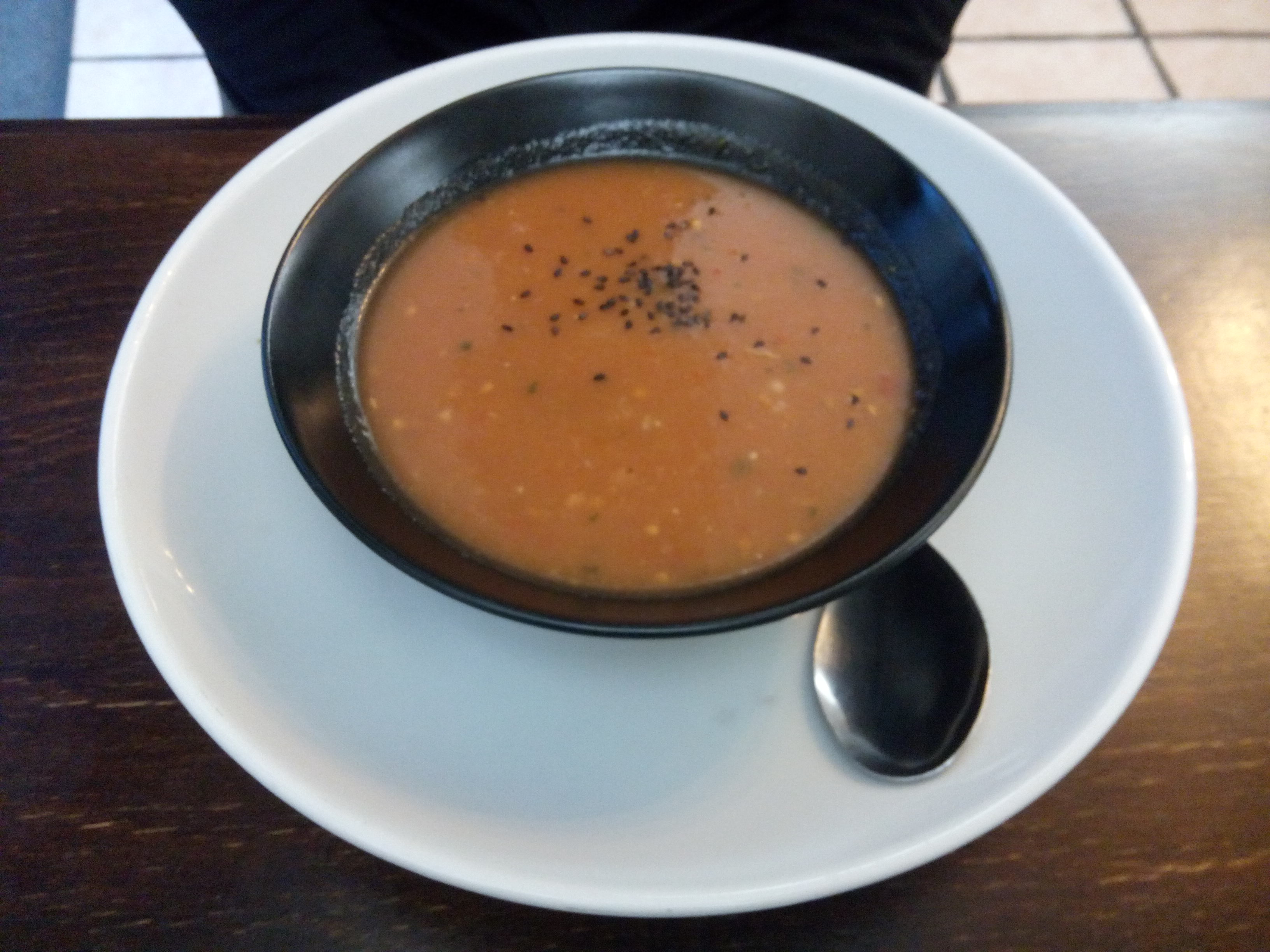 A black bowl containing orange soup on a white plate with a spoon