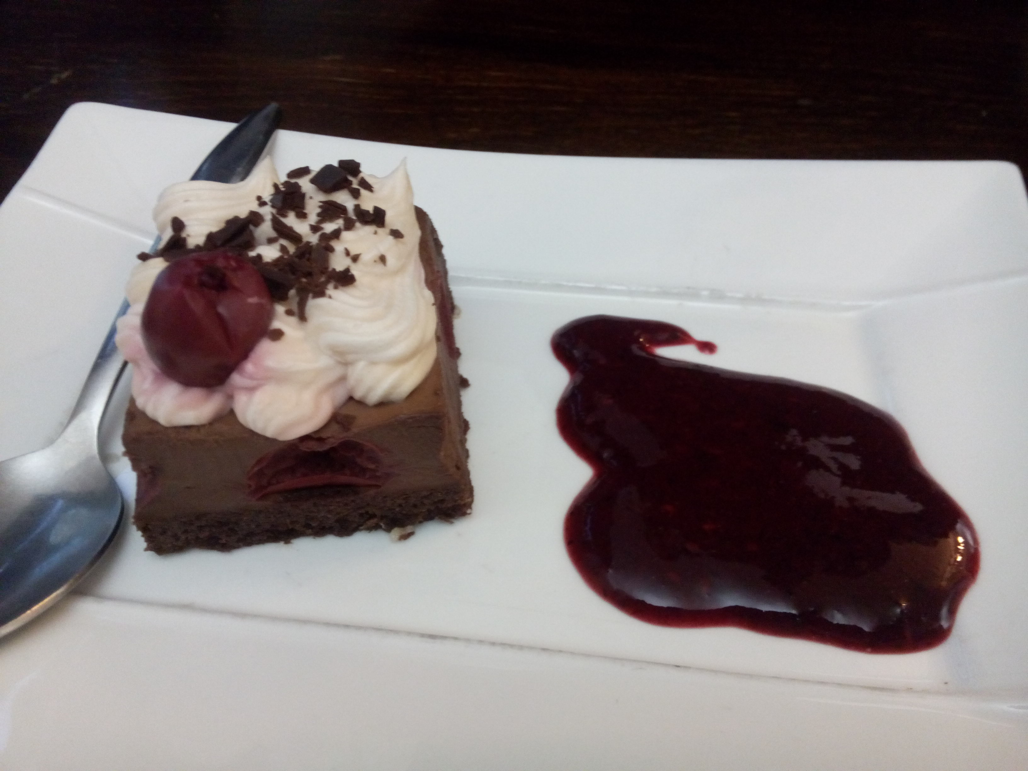 A chocolate square cake with cream and a raspberry on top, next to a blob of fruity sauce