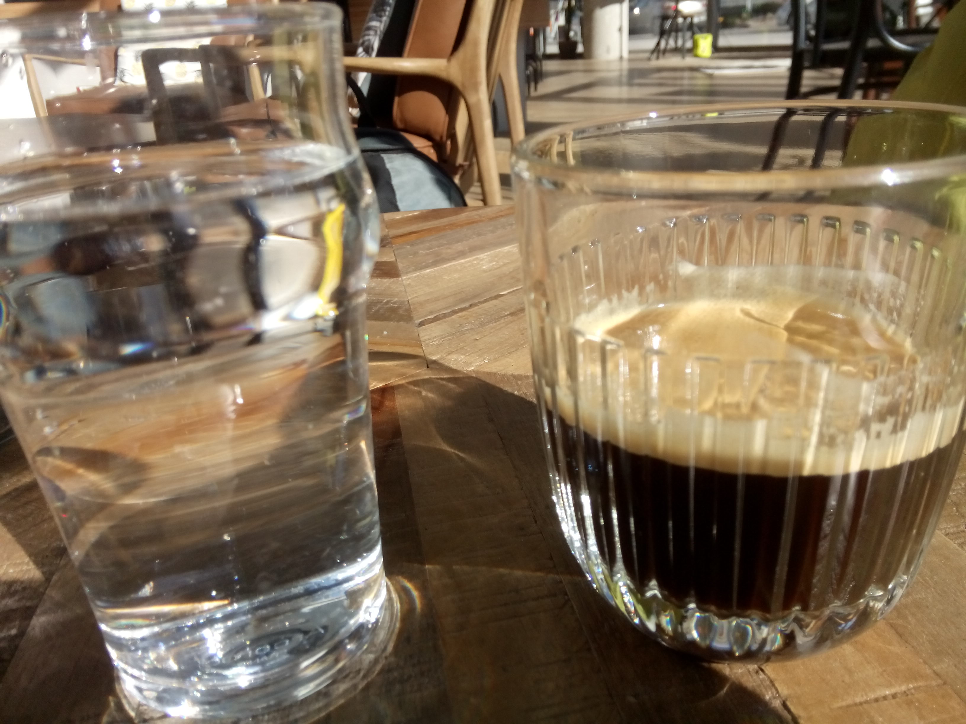 A glass of water on the left and a glass of dark espresso on the right, on a wooden table, with light refracting around and through