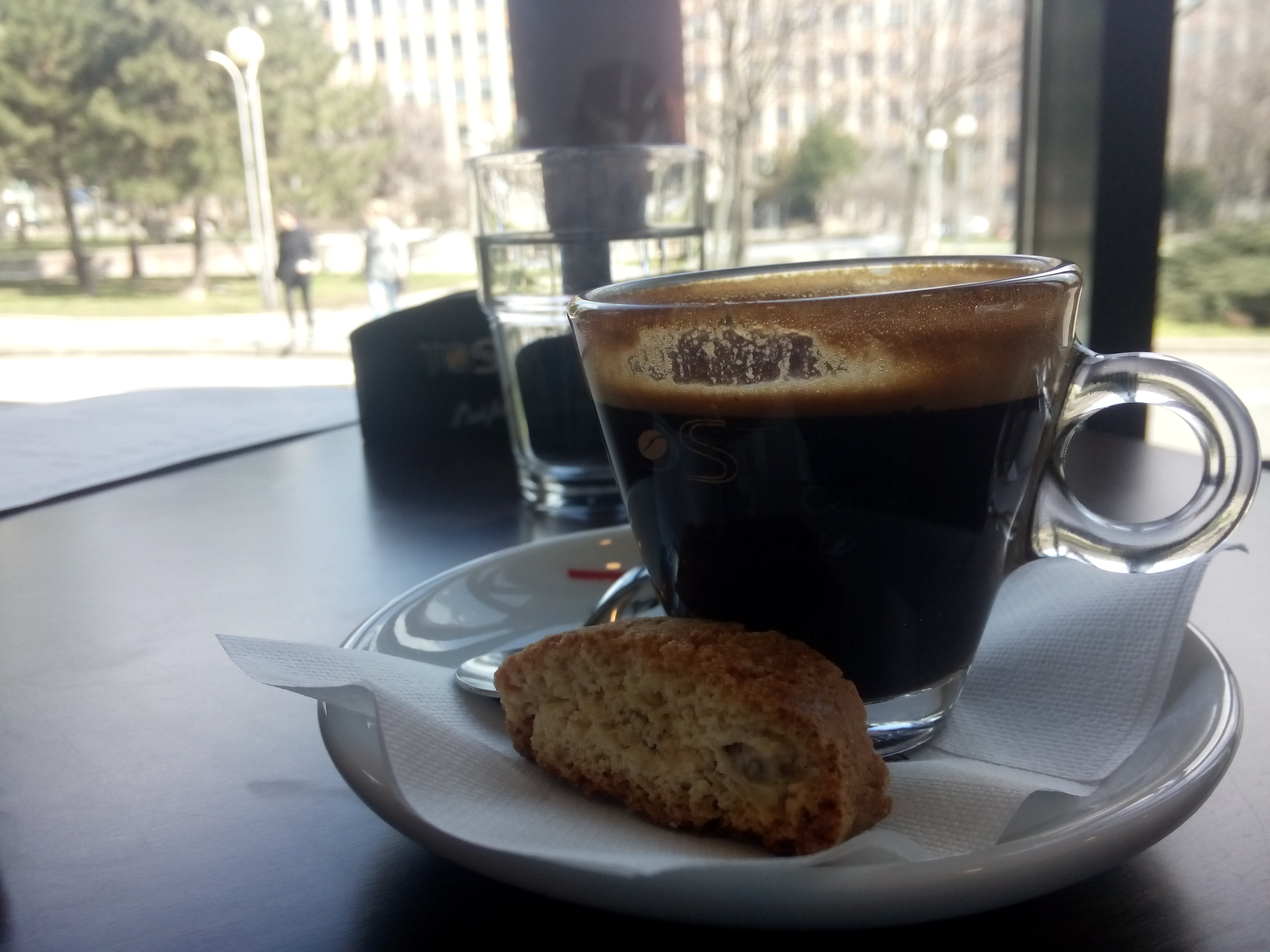 An espresso in a small glass cup on a plate with a biscotti on the side, in front of a window to the street