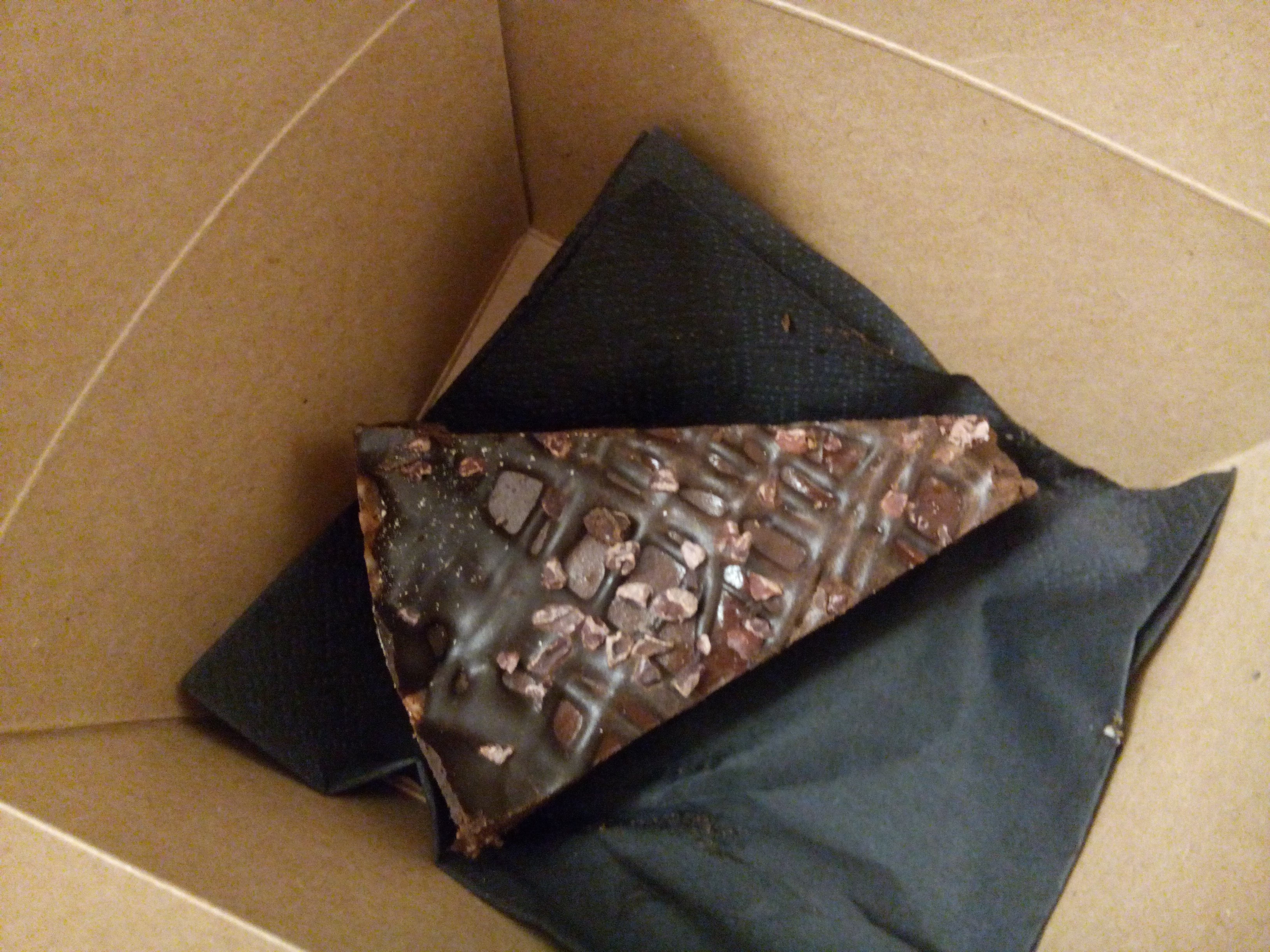 A cardboard box with a black napkin and a slice of chocolate cake from above