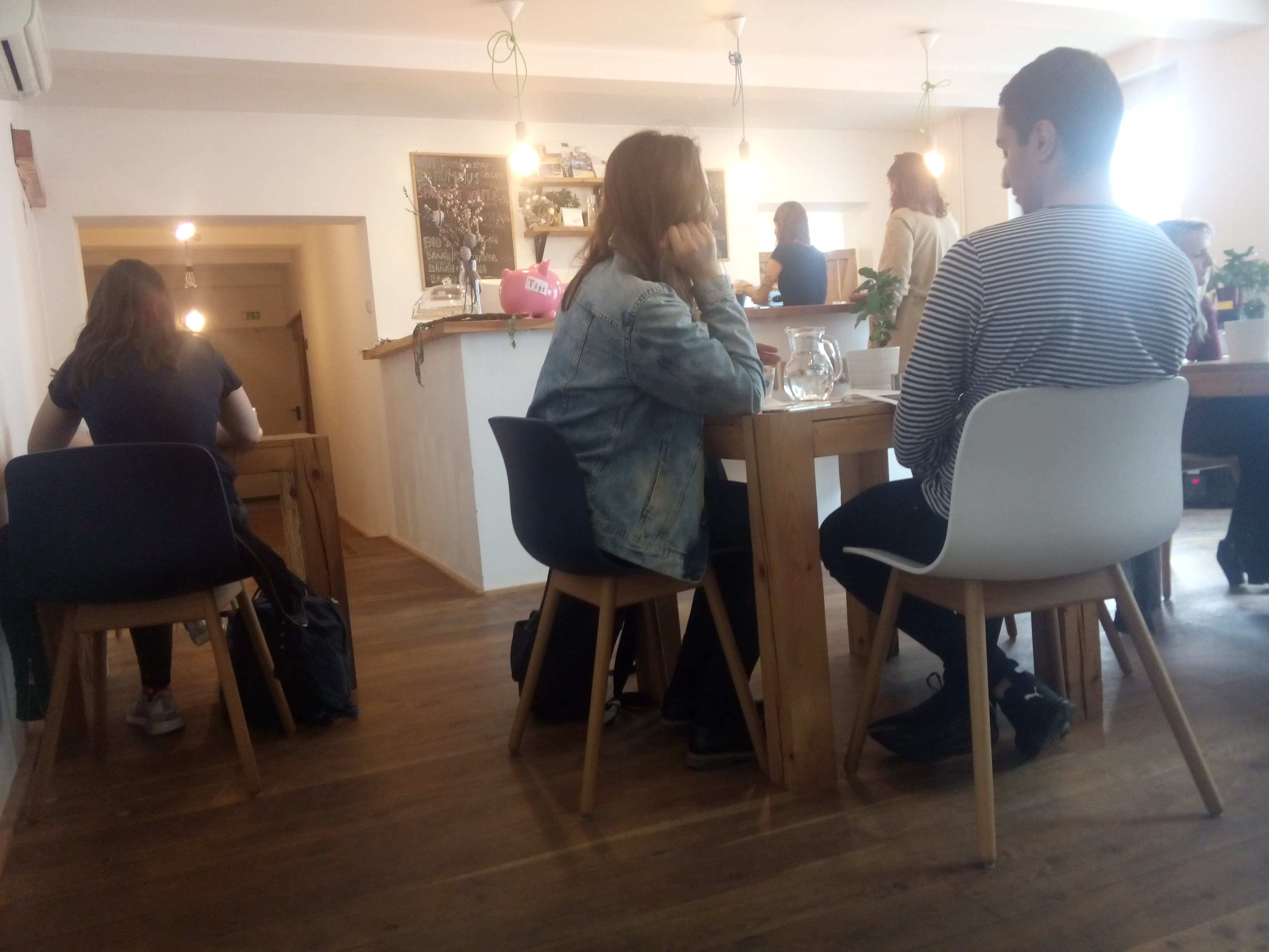 Inside a cafe with aw ooden floor, white seats, and people chatting at a table
