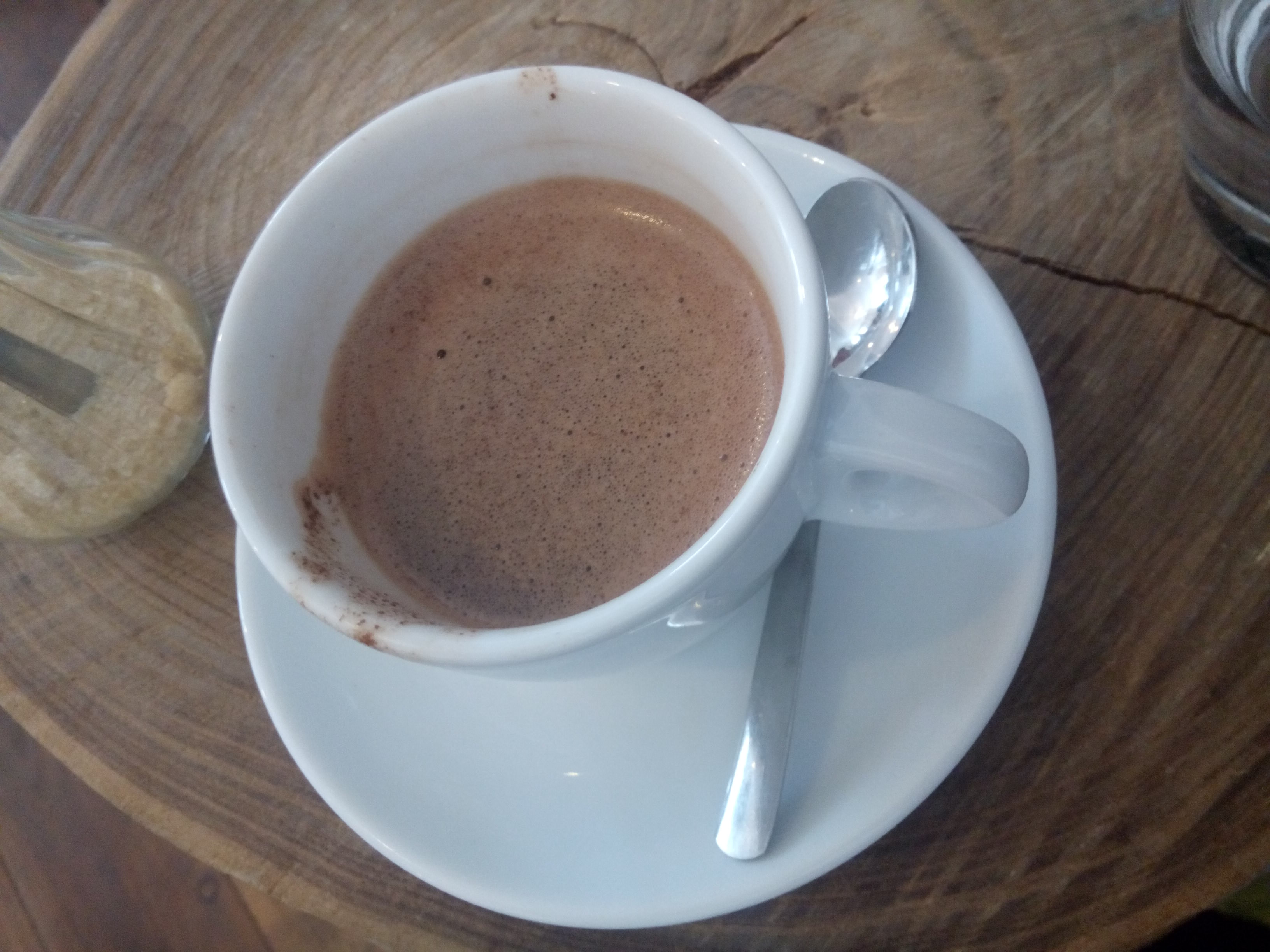 A wooden table with a white cup of hot chocolate from above