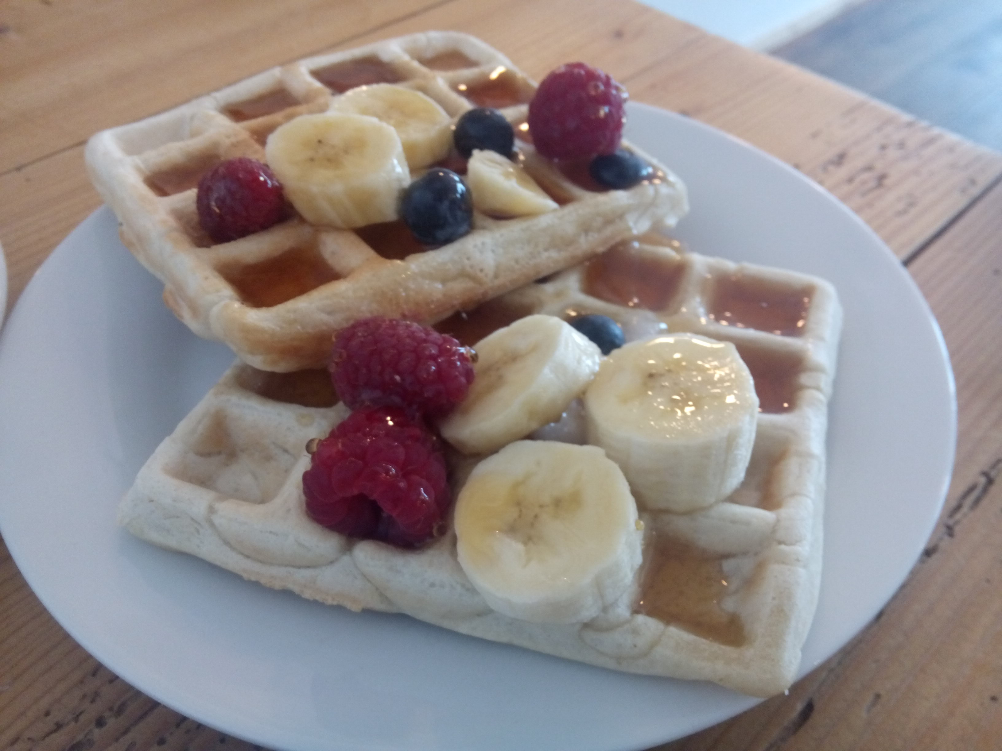 Two waffles on a plate with syrup, banana, blueberries and raspberries