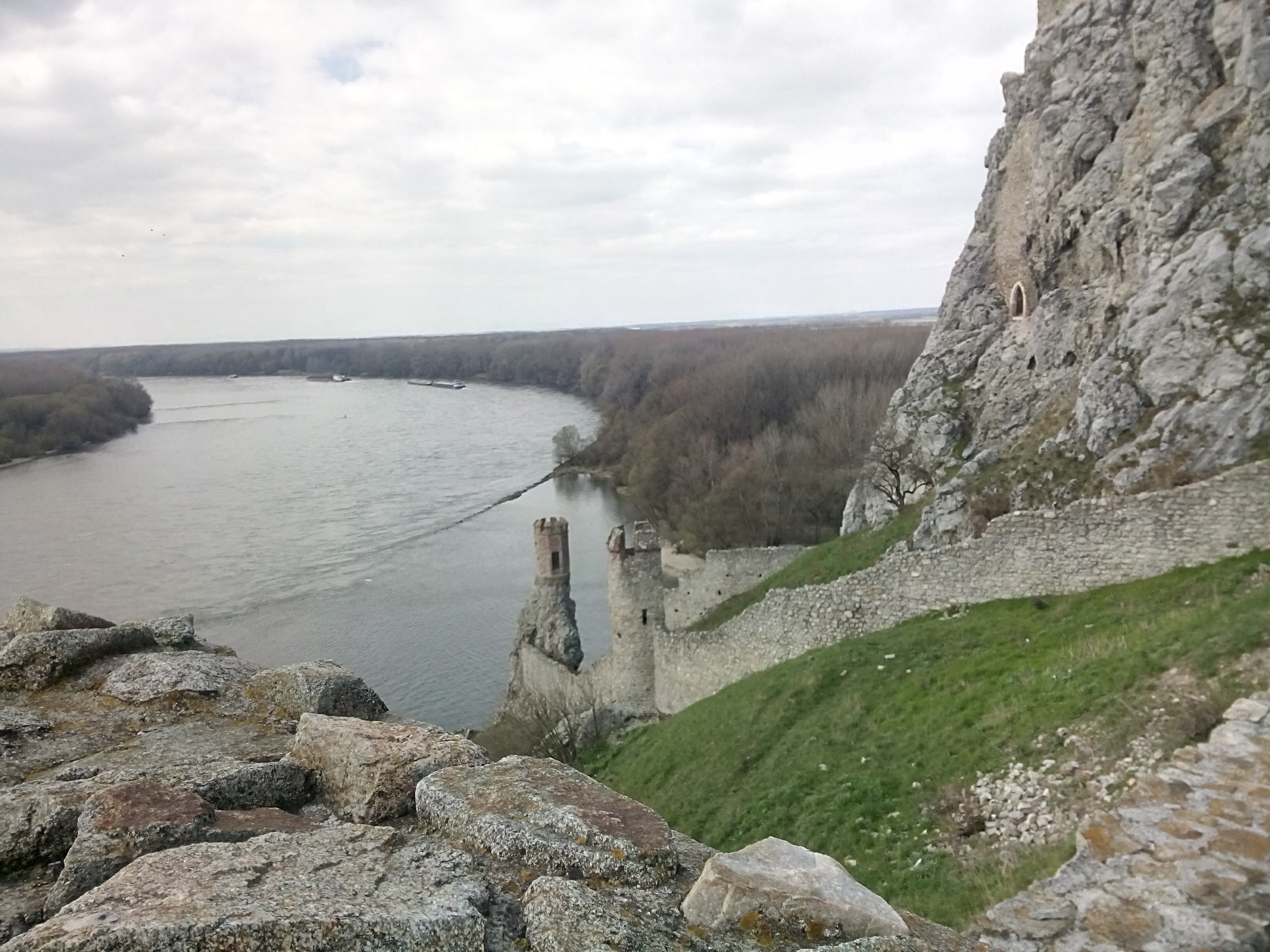 A rocky cliff to the right overlooking a curve in the river, the banks lined by bare trees