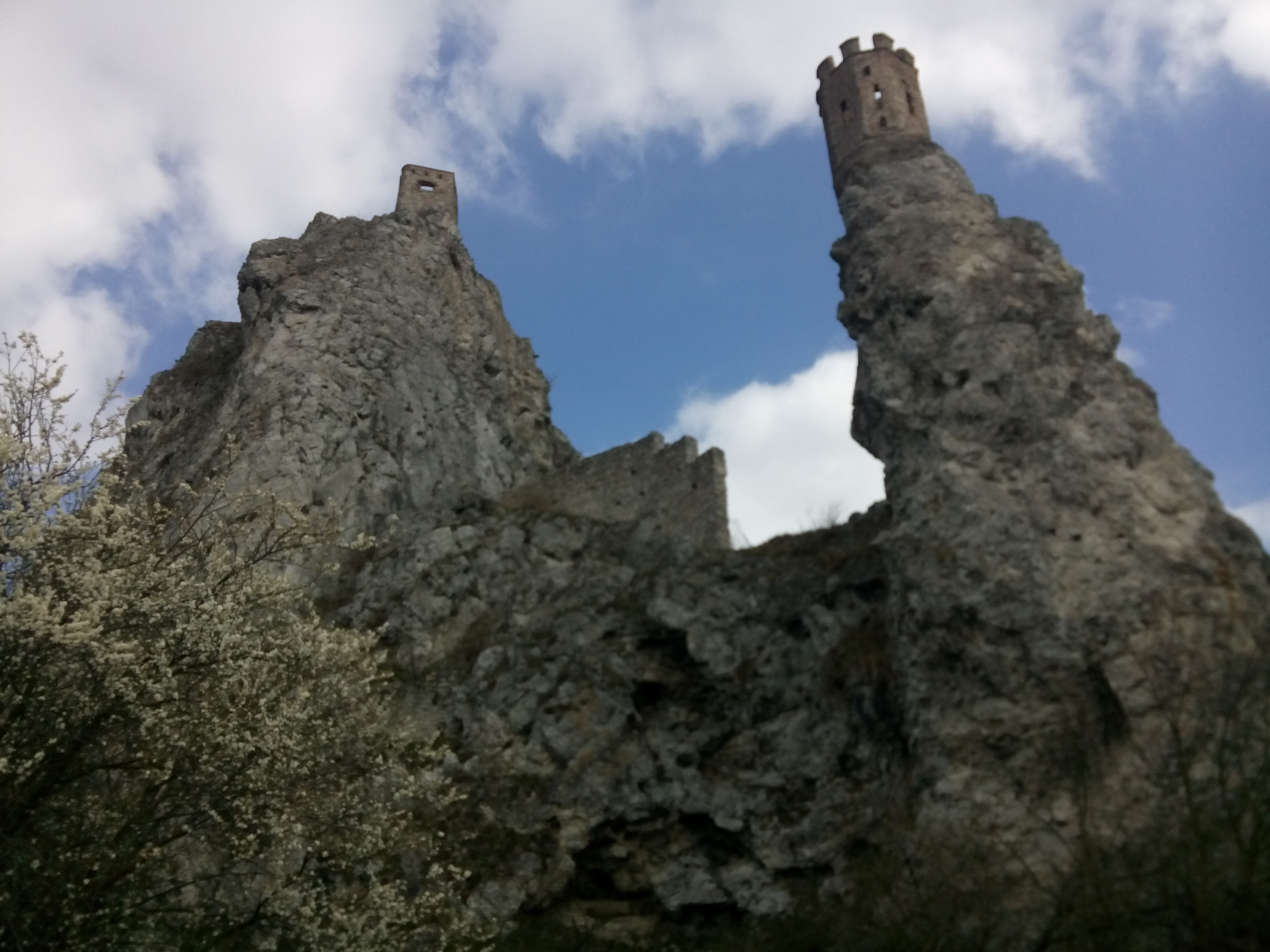 View from below, looking up a rugged cliff topped with a small turreted tower, against blue and white sky