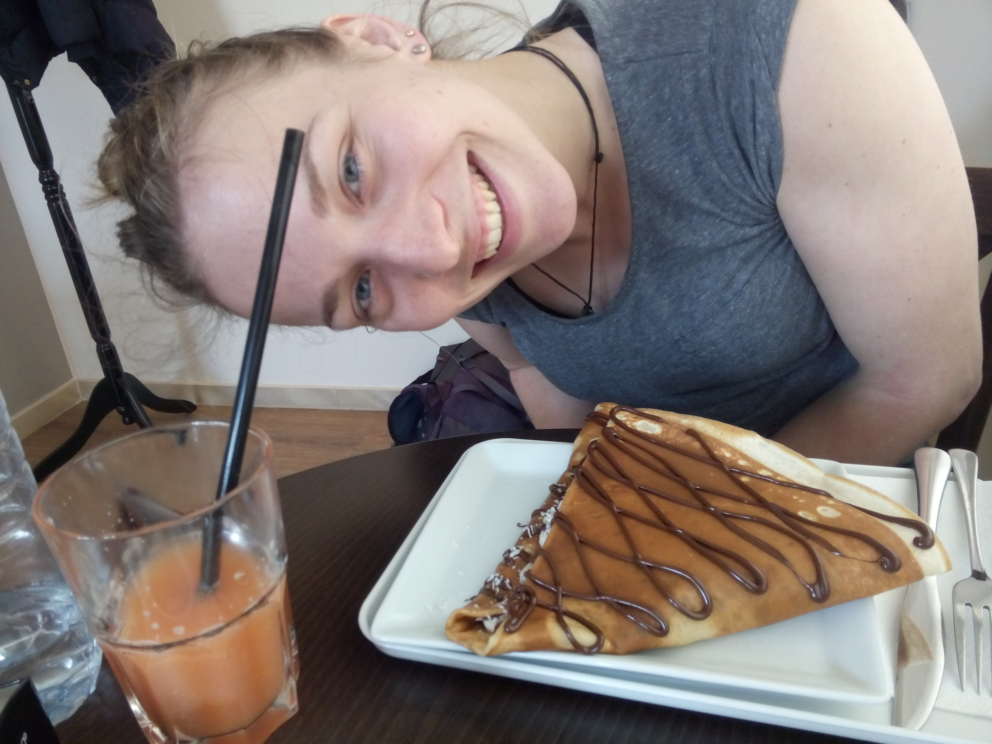 A woman in a grey tshirt leans sideways smiling over a crepe on aplate and a glass of grapefruit juice with a straw