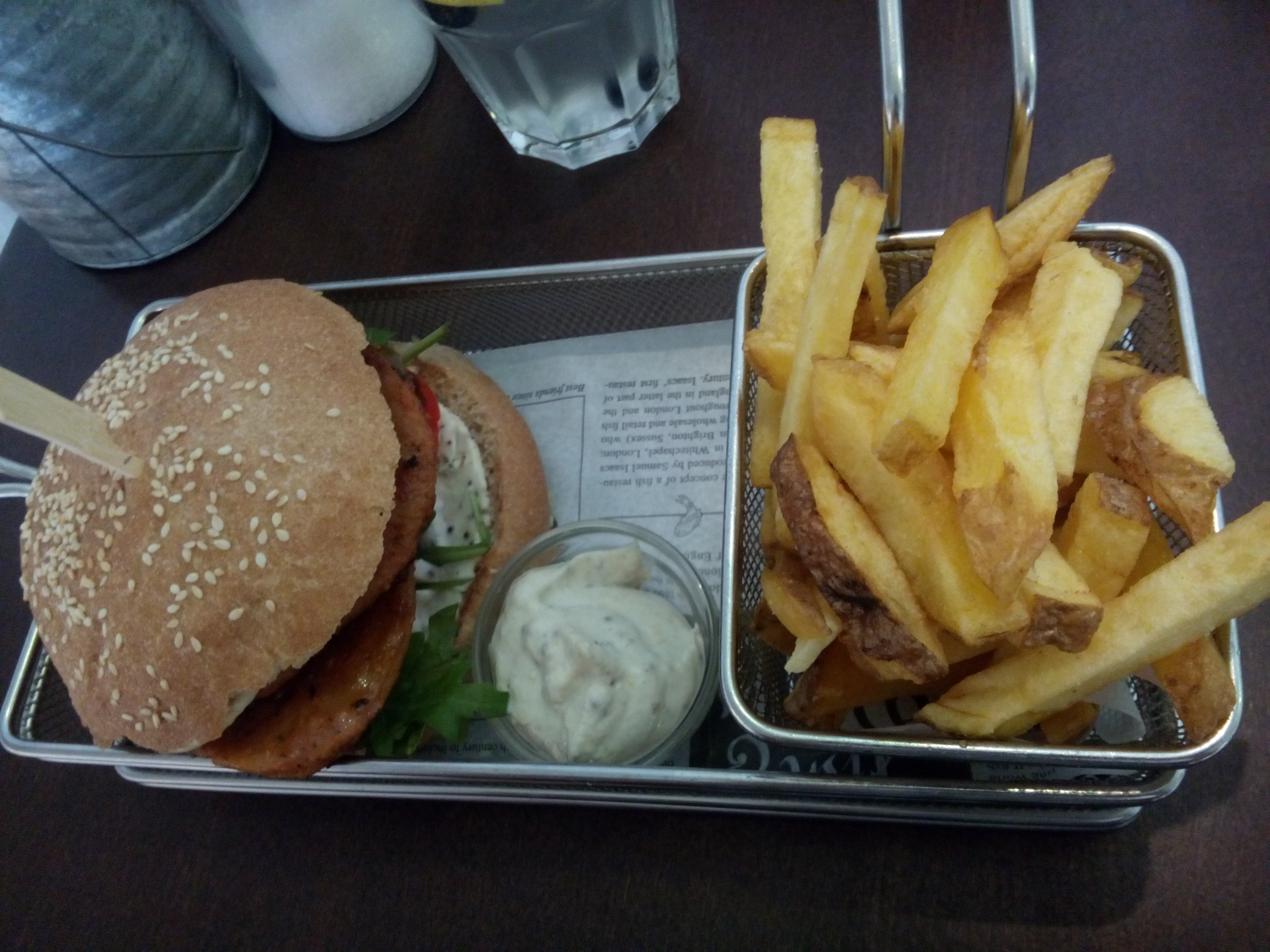 A metal basket with fries, a small pot of mayo and a burger from above