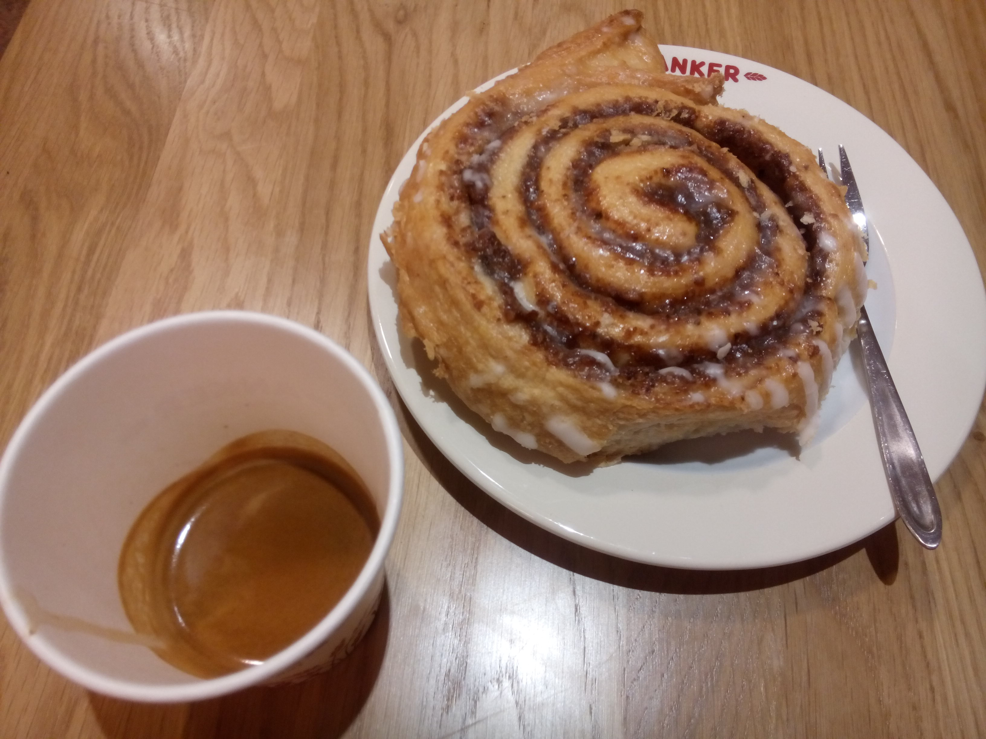 A wooden table, espresso in a takeaway cup and a spiral pastry on a plate