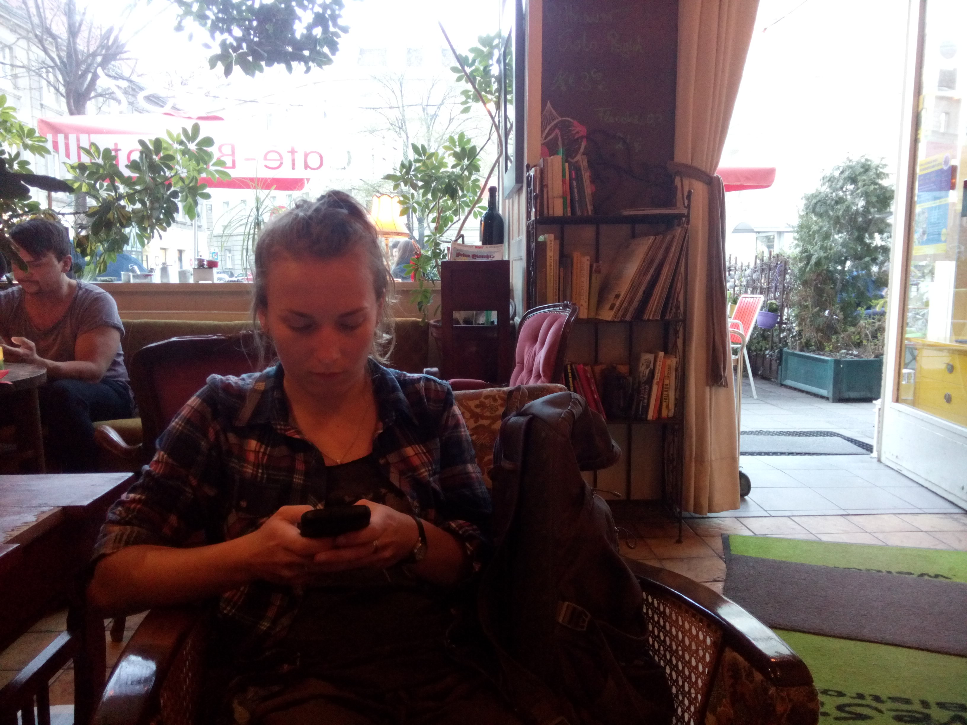 A woman with hair tied back and a checked shirt, texting, sitting in a cafe with books on a shelf in the background