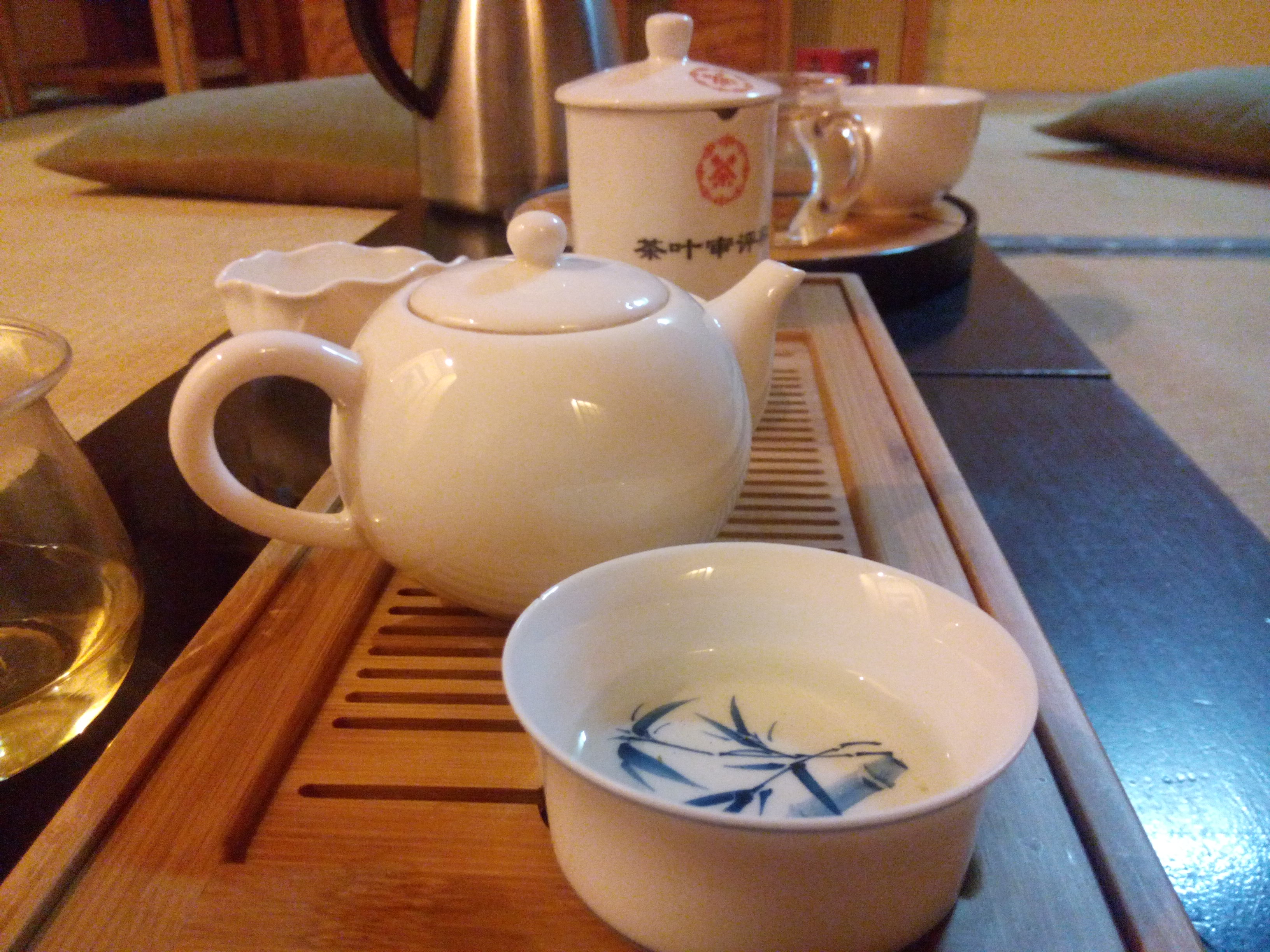 A white cup and teapot on a wooden board