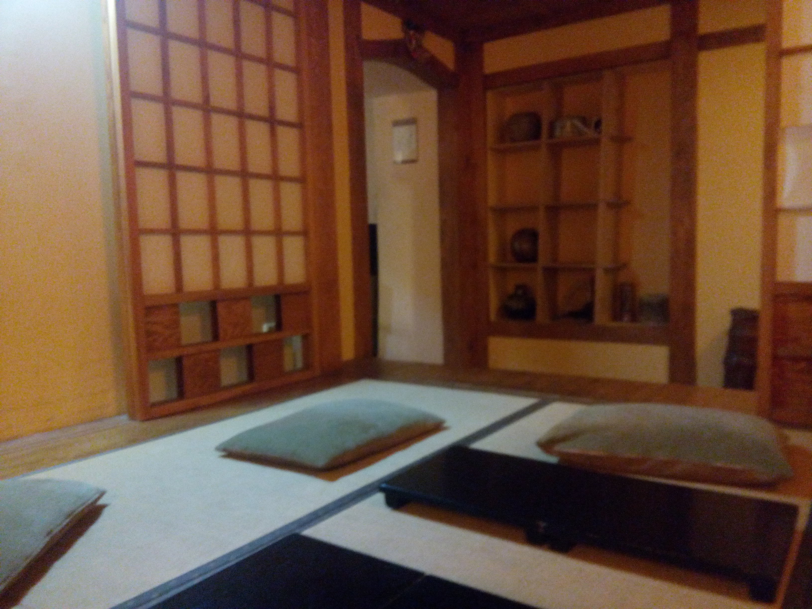 A room with wooden and paper panels in the walls and cushions on the floor