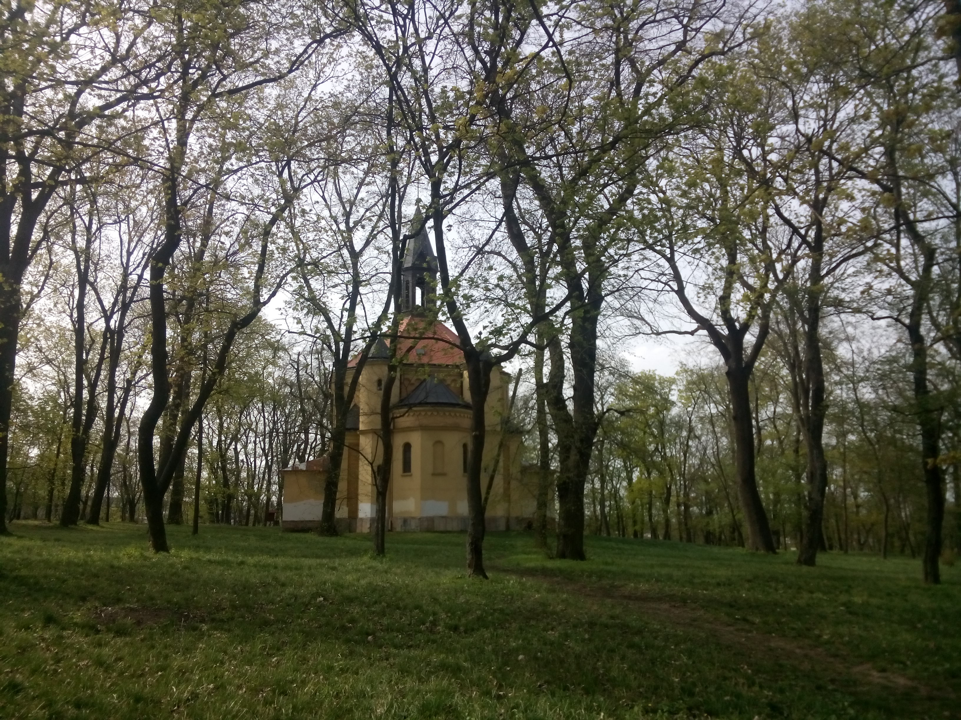 A yellow brick round church behind some trees