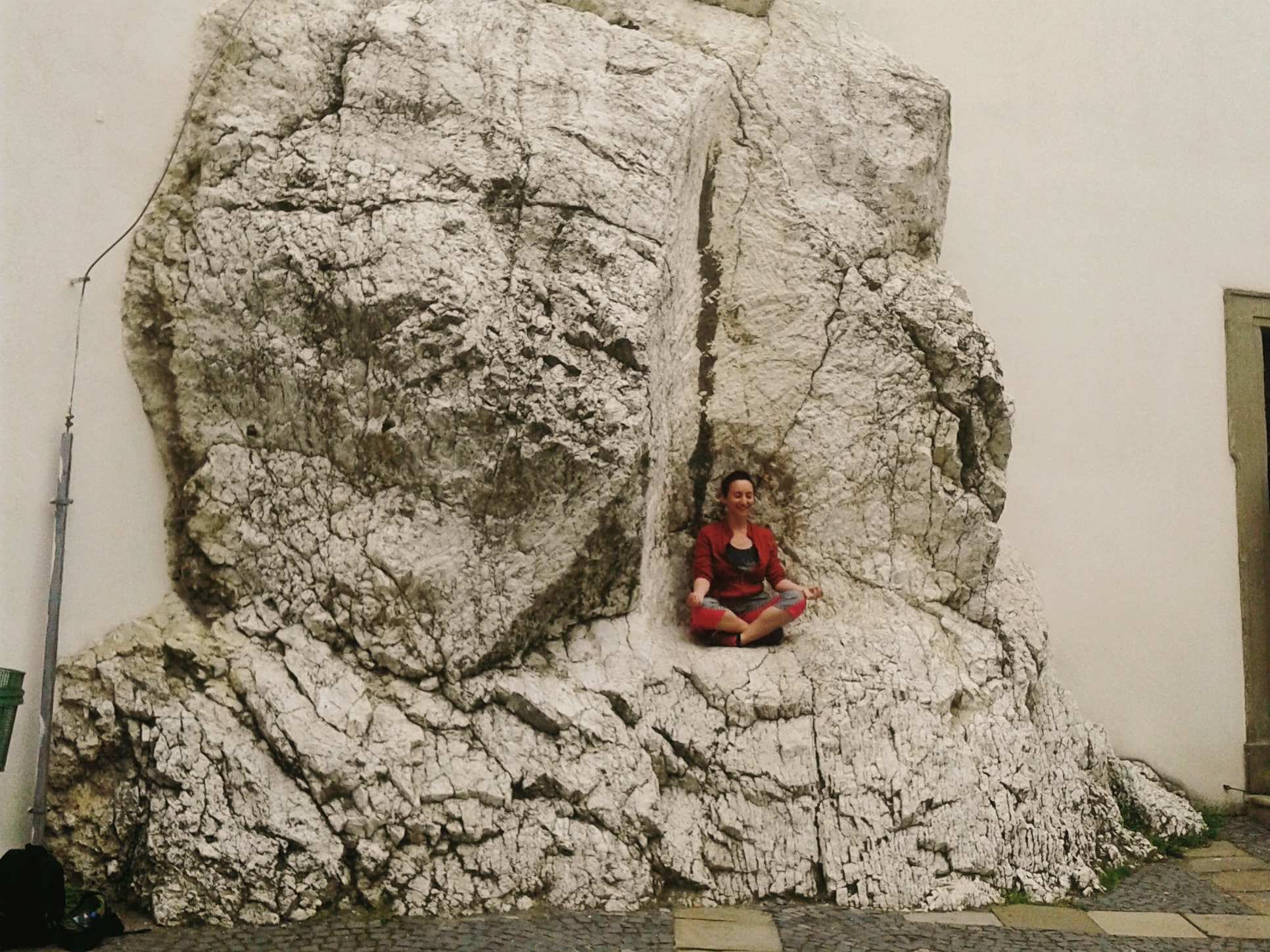 rhiaro in a red jacket sits cross-legged on a little shelf in a big rock
