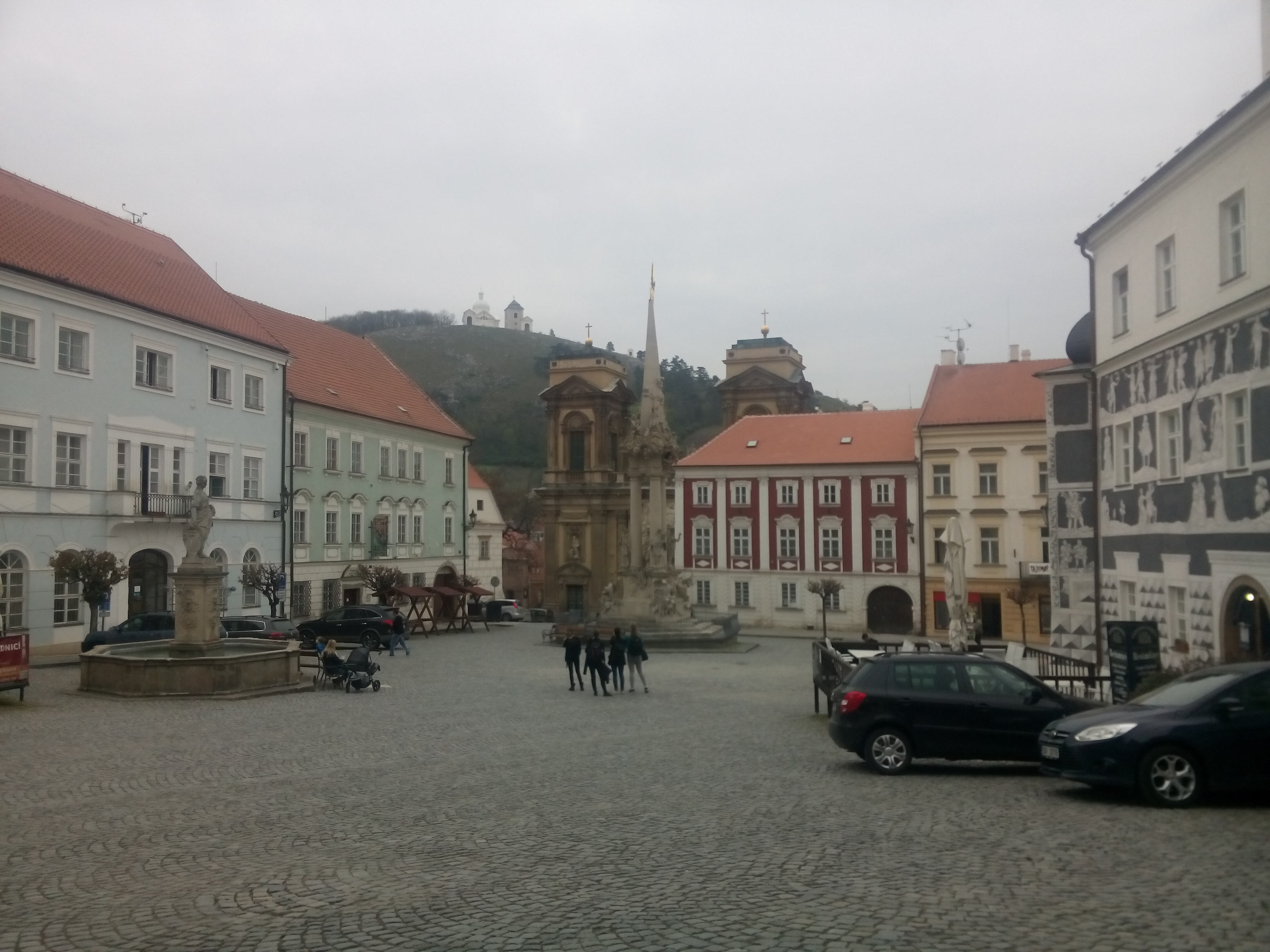 A cobbled town square with a couple of cars and a tower in the middle and a hill in the backgrounds