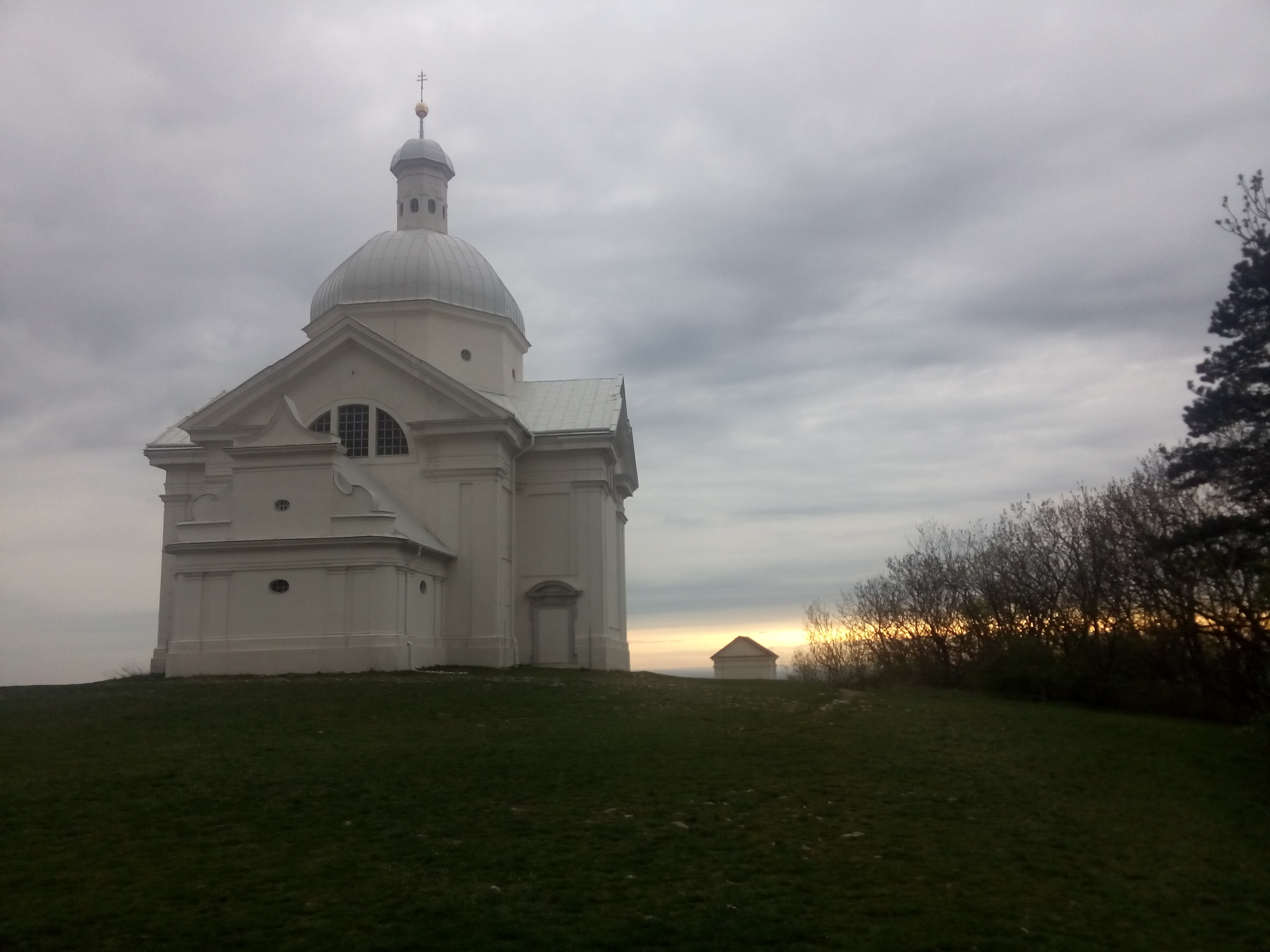 A white church on a grass field against a cloudy sky, with a sliver of sunset on the horizon