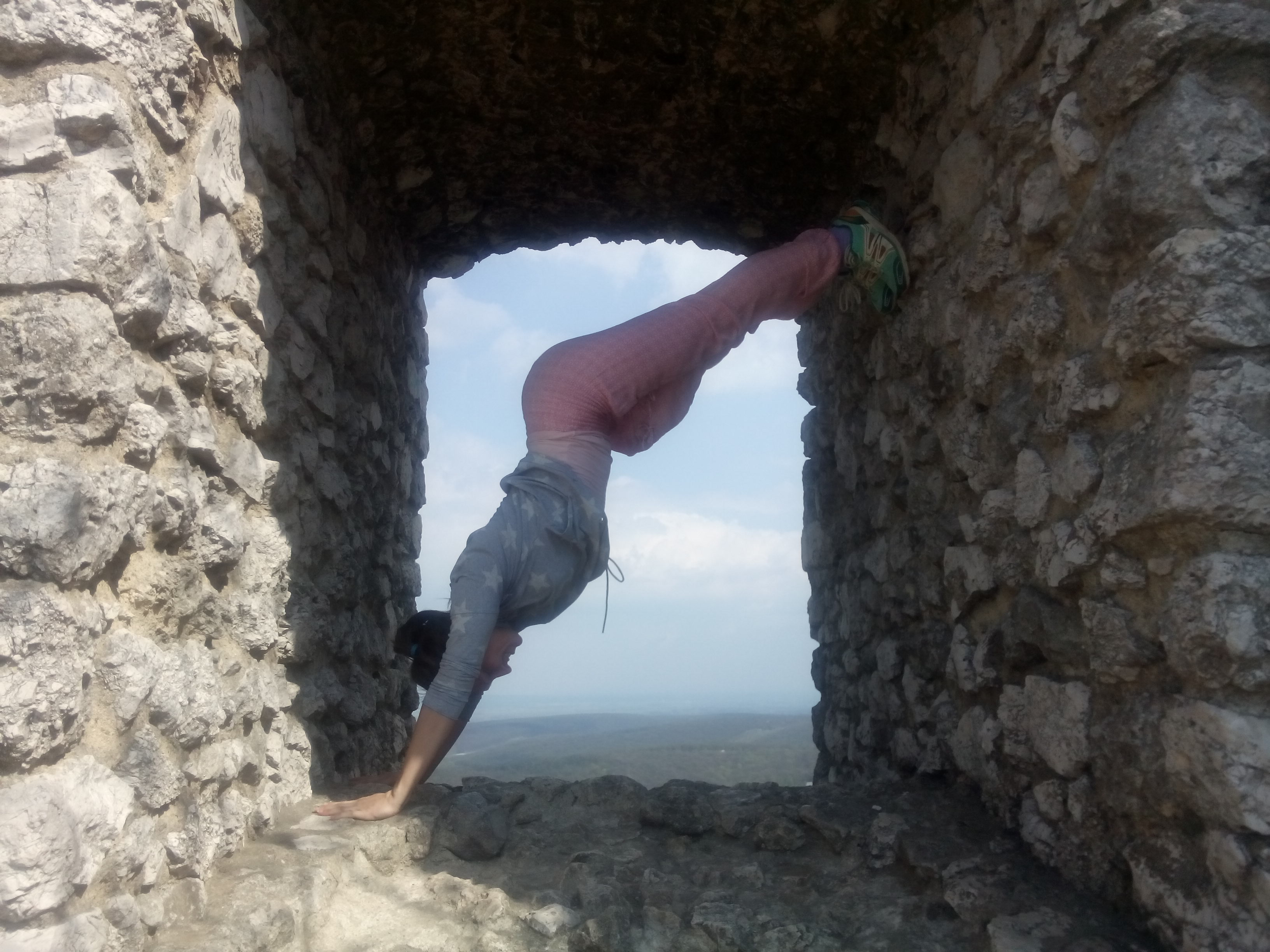 A woman in a blue shirt and pink tights wedged upside down in a stone window