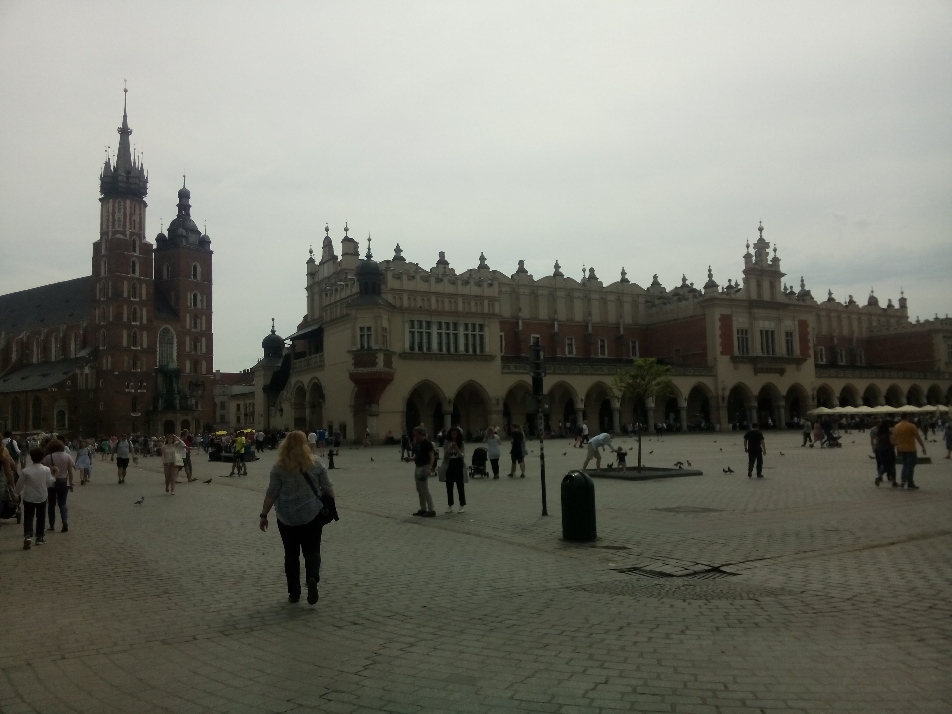 A cobbled square with walking people and fancy buildings