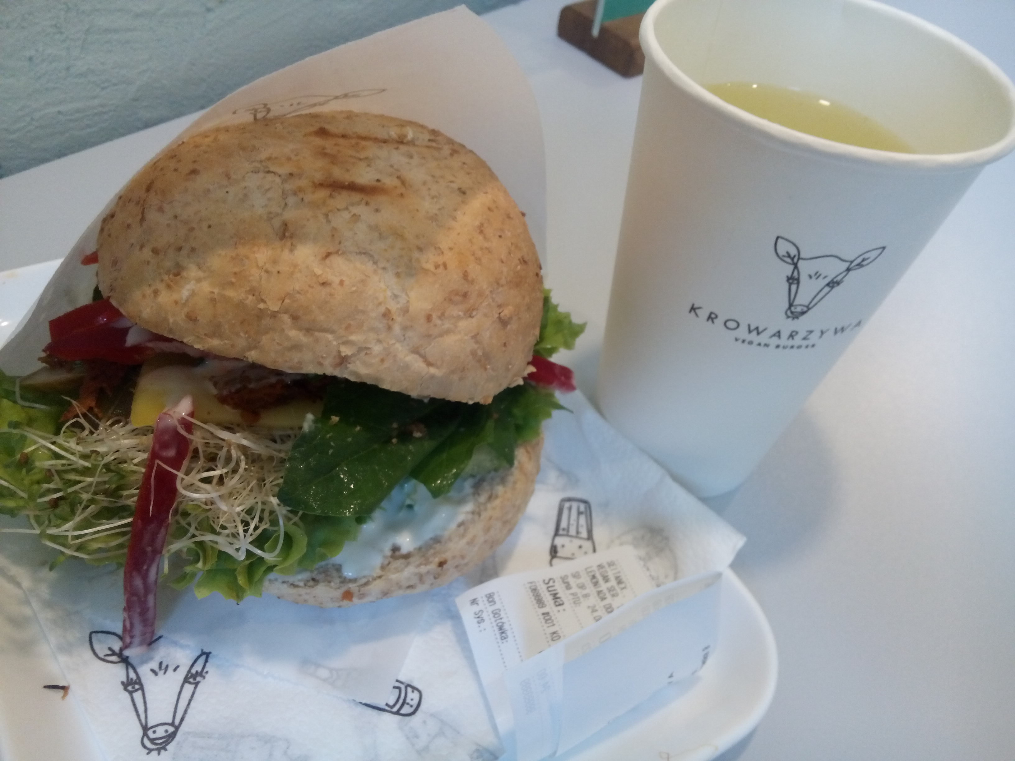 A paper cup with a line drawing of a cow and something yellow in, and a tray with a burger, brown bun exploding with salad and sprouts