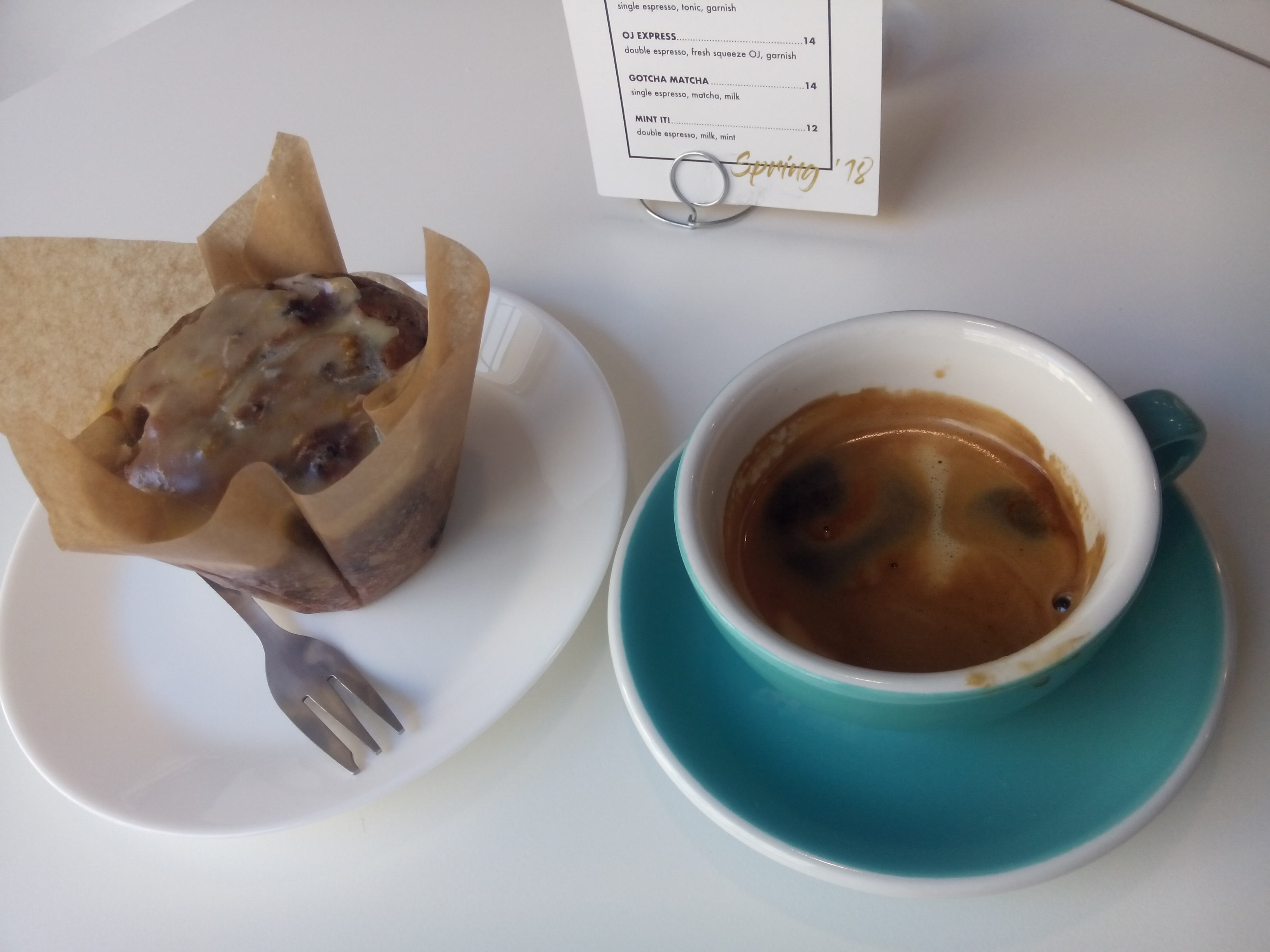 A plate with a muffin in brown paper next to a double espresso in a blue and white cup