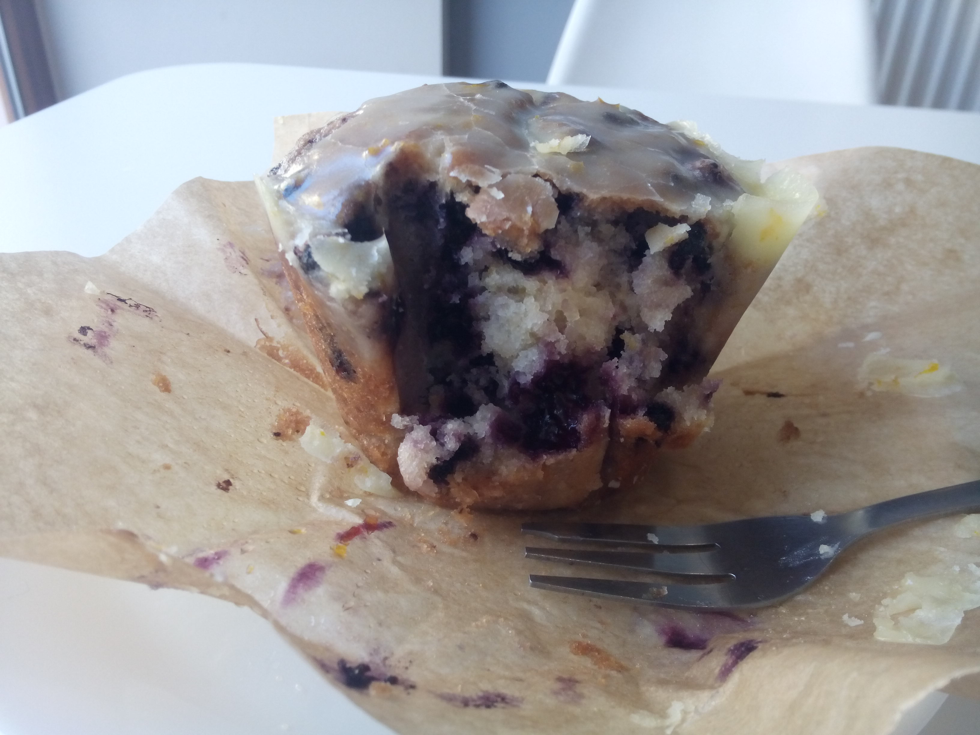 A half eaten muffin from the front, exposing purple berry blotches and crusted with lemon frosting