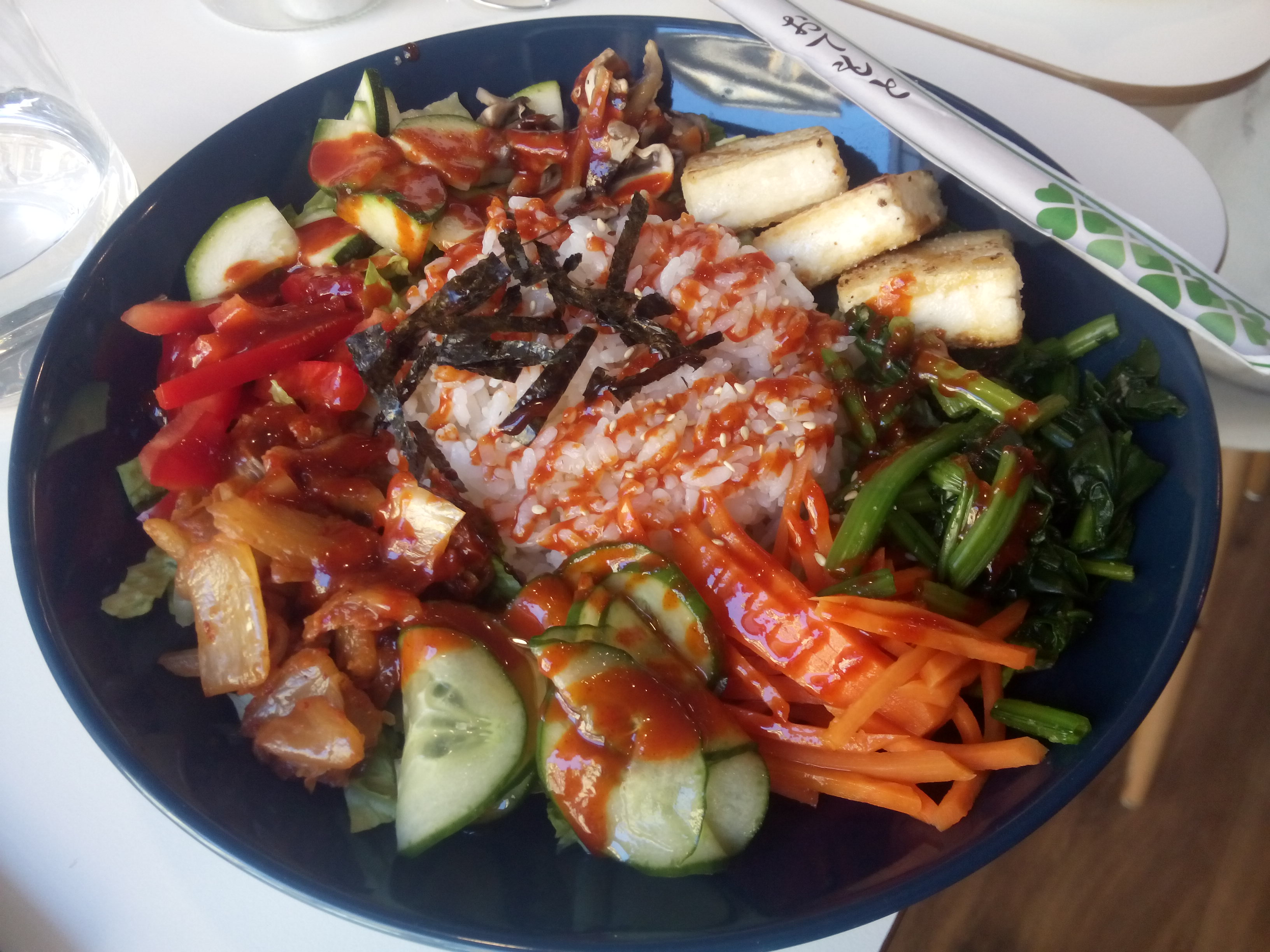 A black bowl with colourful salad and tofu, drizzled liberally with chilli sauce