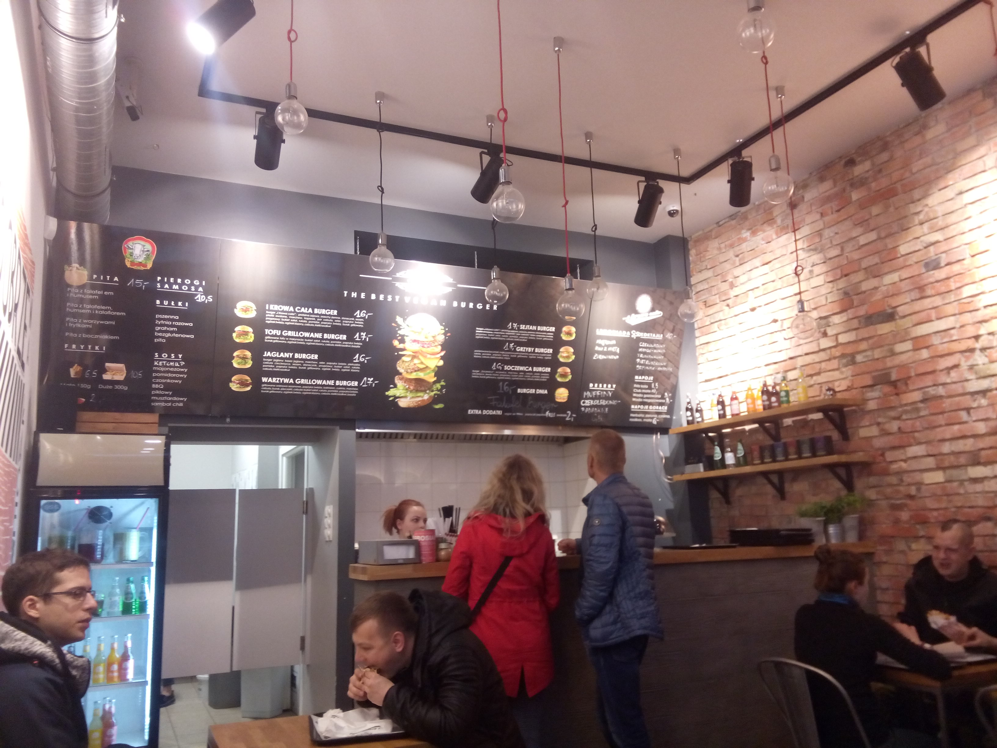 A brick interior of a modern cafe, with a menu on the wall above the counter, and some people sitting or standing around