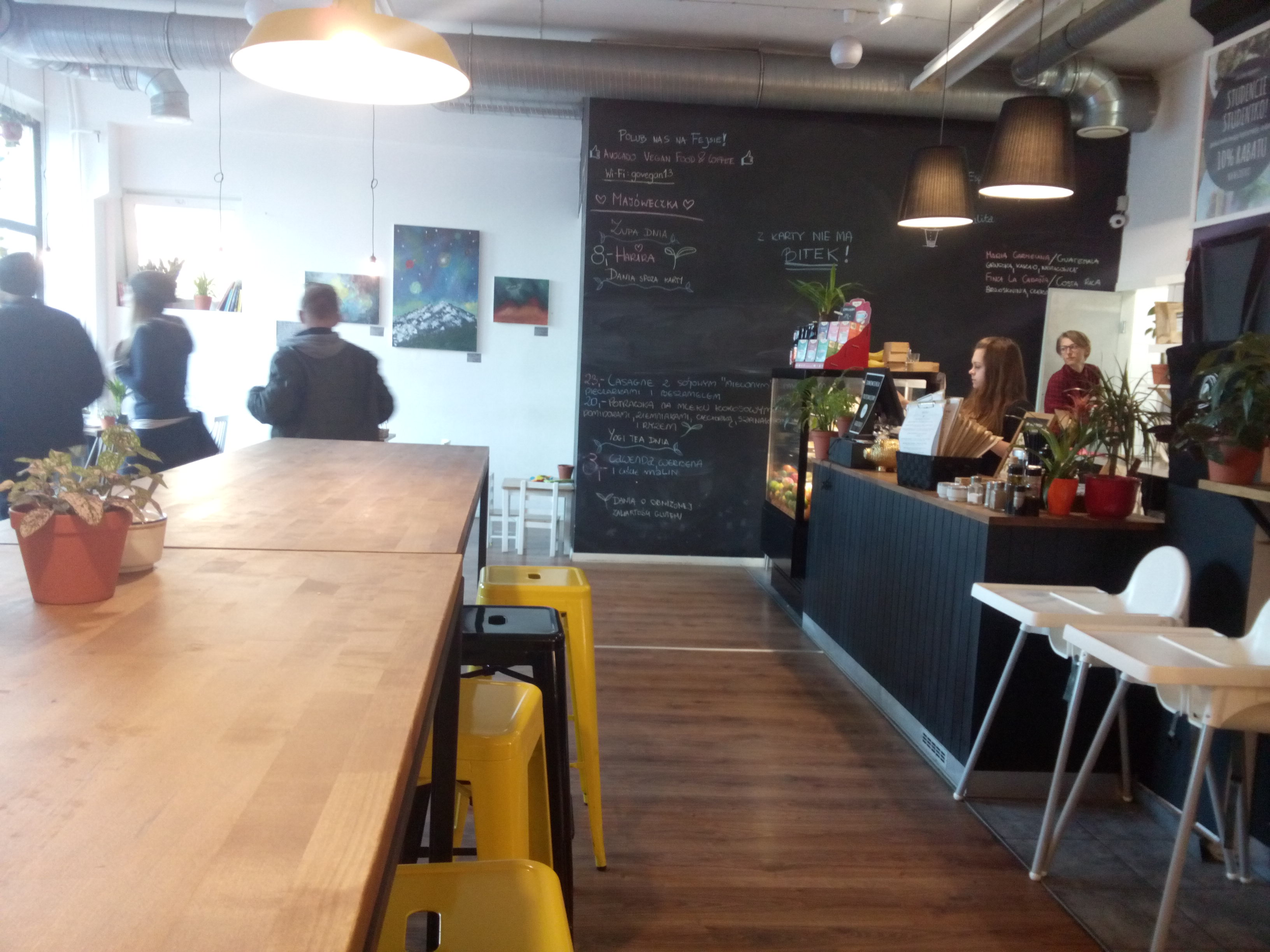 A cafe with wooden tables, blue walls and al arge blackboard beside the counter