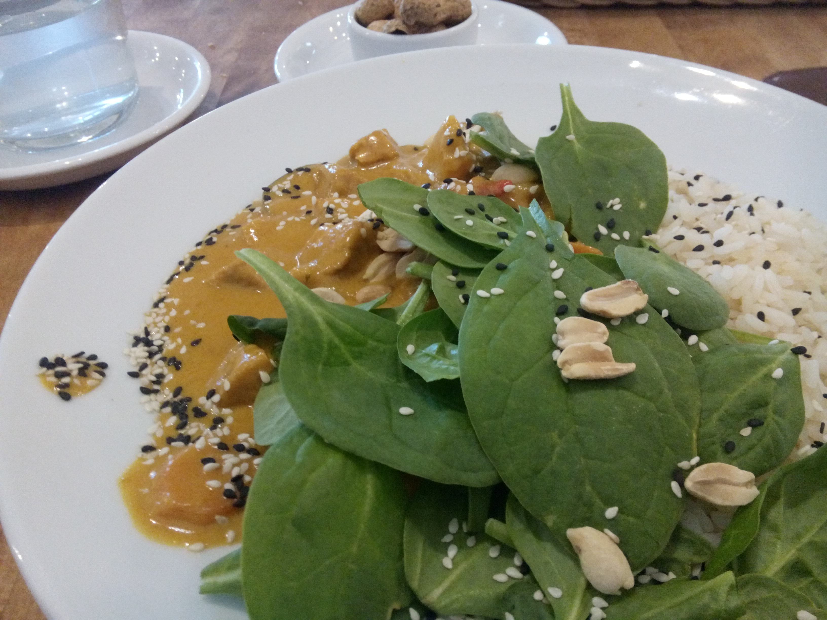 A white plate with creamy orange curry sprinkled with sesame seeds, fresh spinach and peanuts