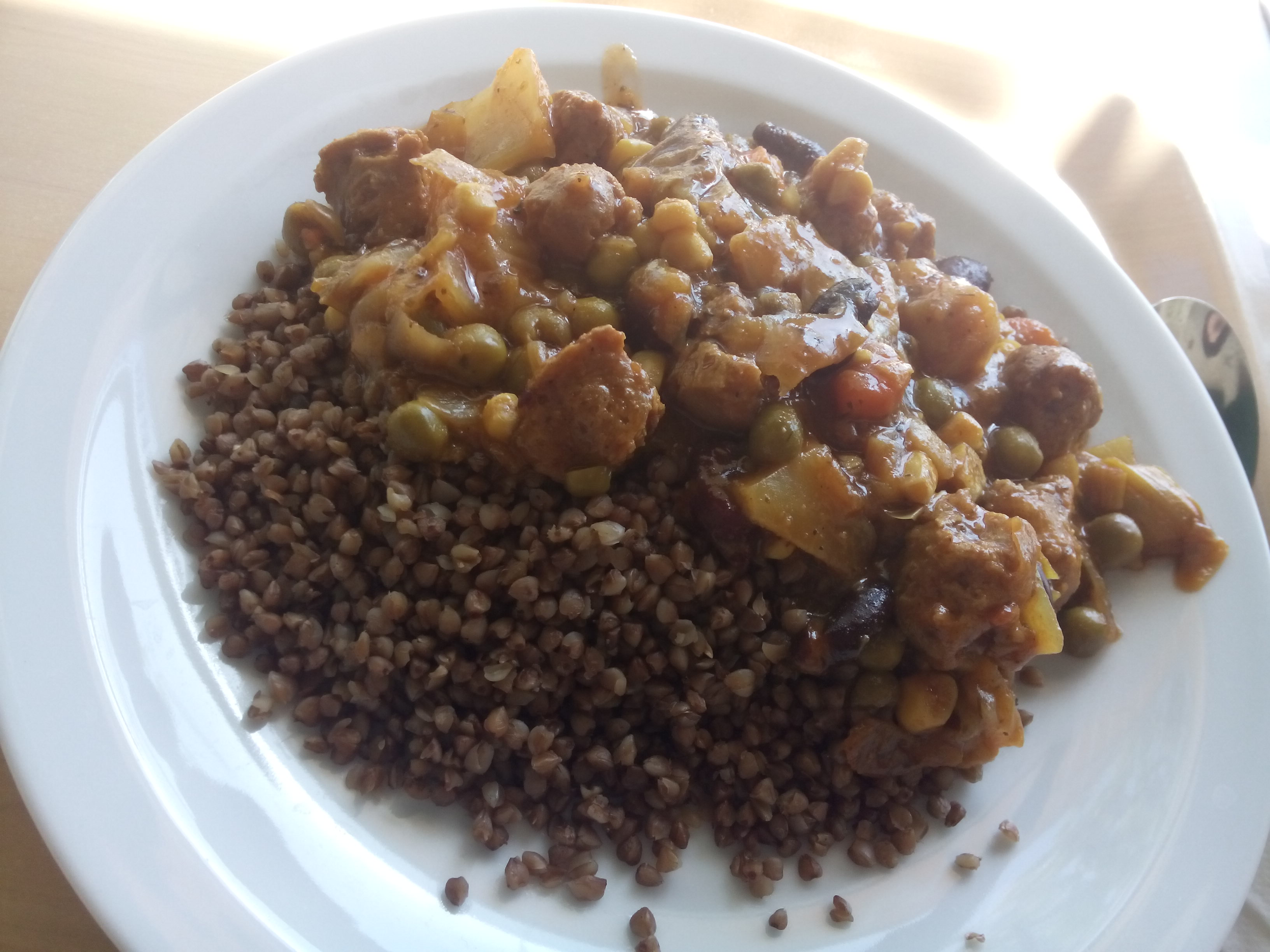 A white plate with half buckwheat and half vegetable soya goulash