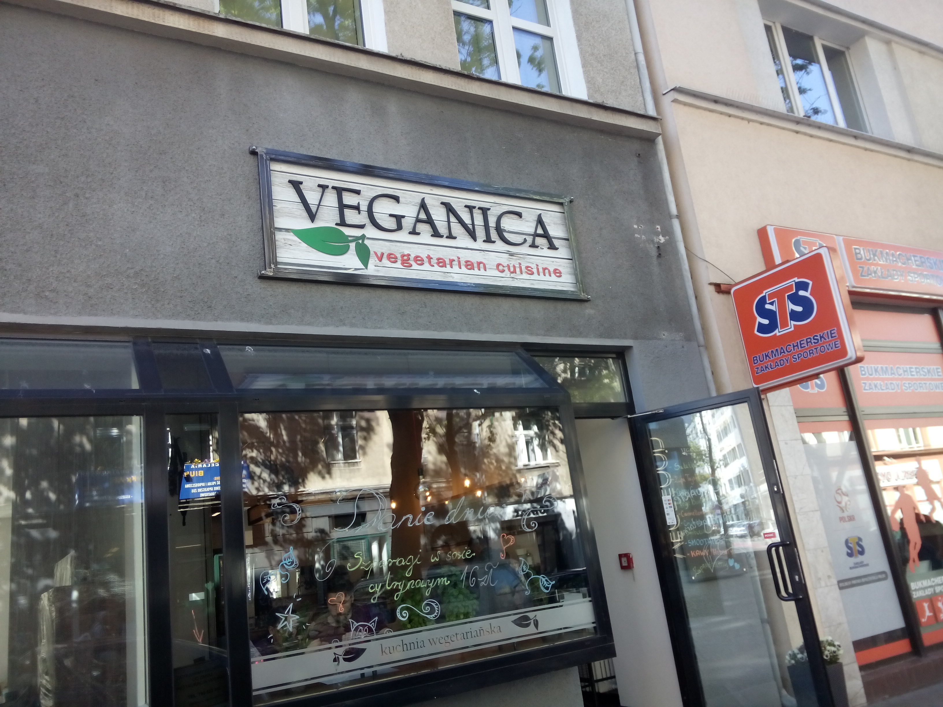 A concrete-fronted shop, glass window, and 'veganica' sign.