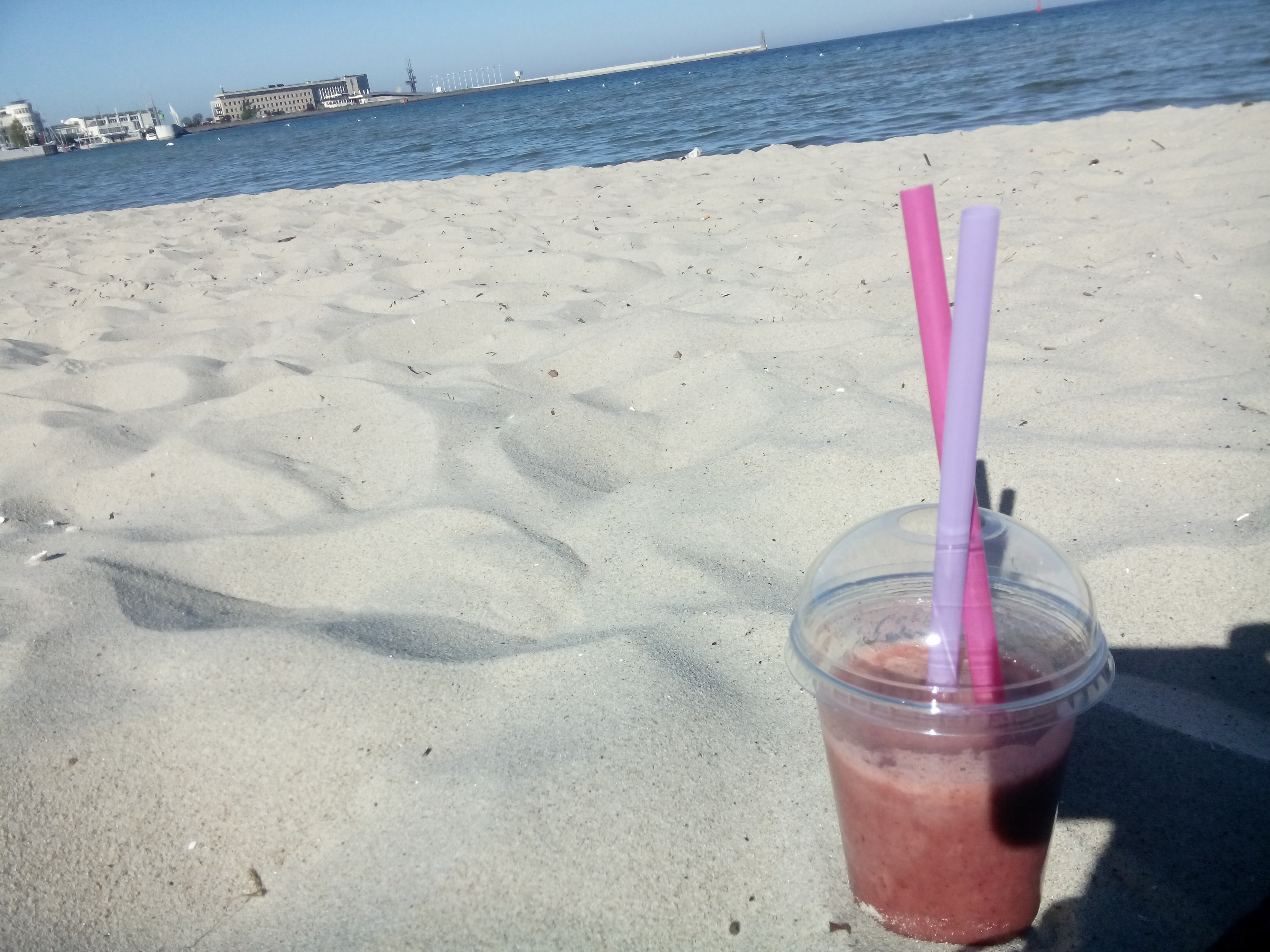 A pink smoothie with two straws nestled in beach sand, with the sea and blue sky in the distance