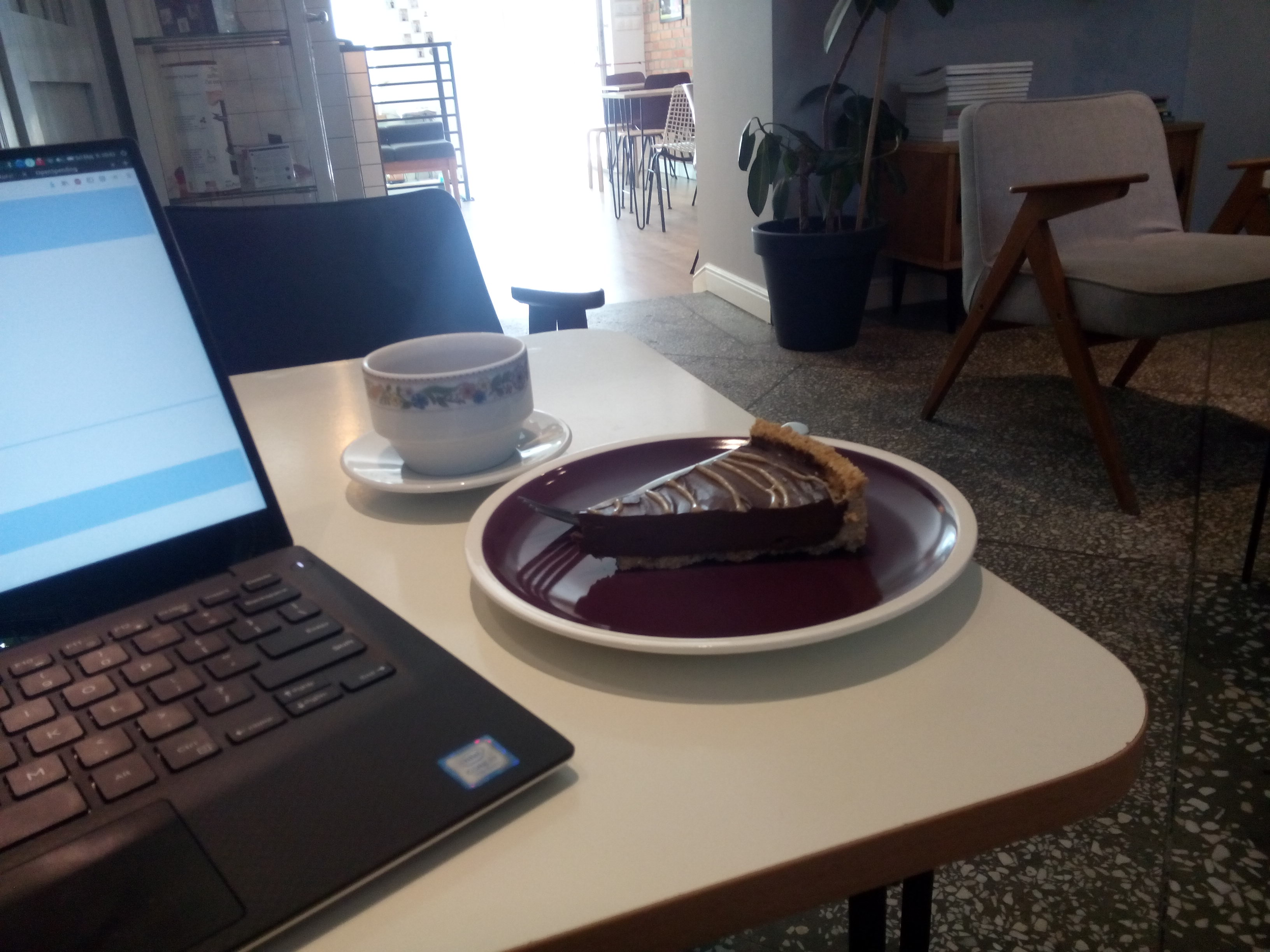 A table with a laptop on the left, and a cup of coffee and a plate with chocolate cake on it to the right; light coming in the cafe entrance in the distance