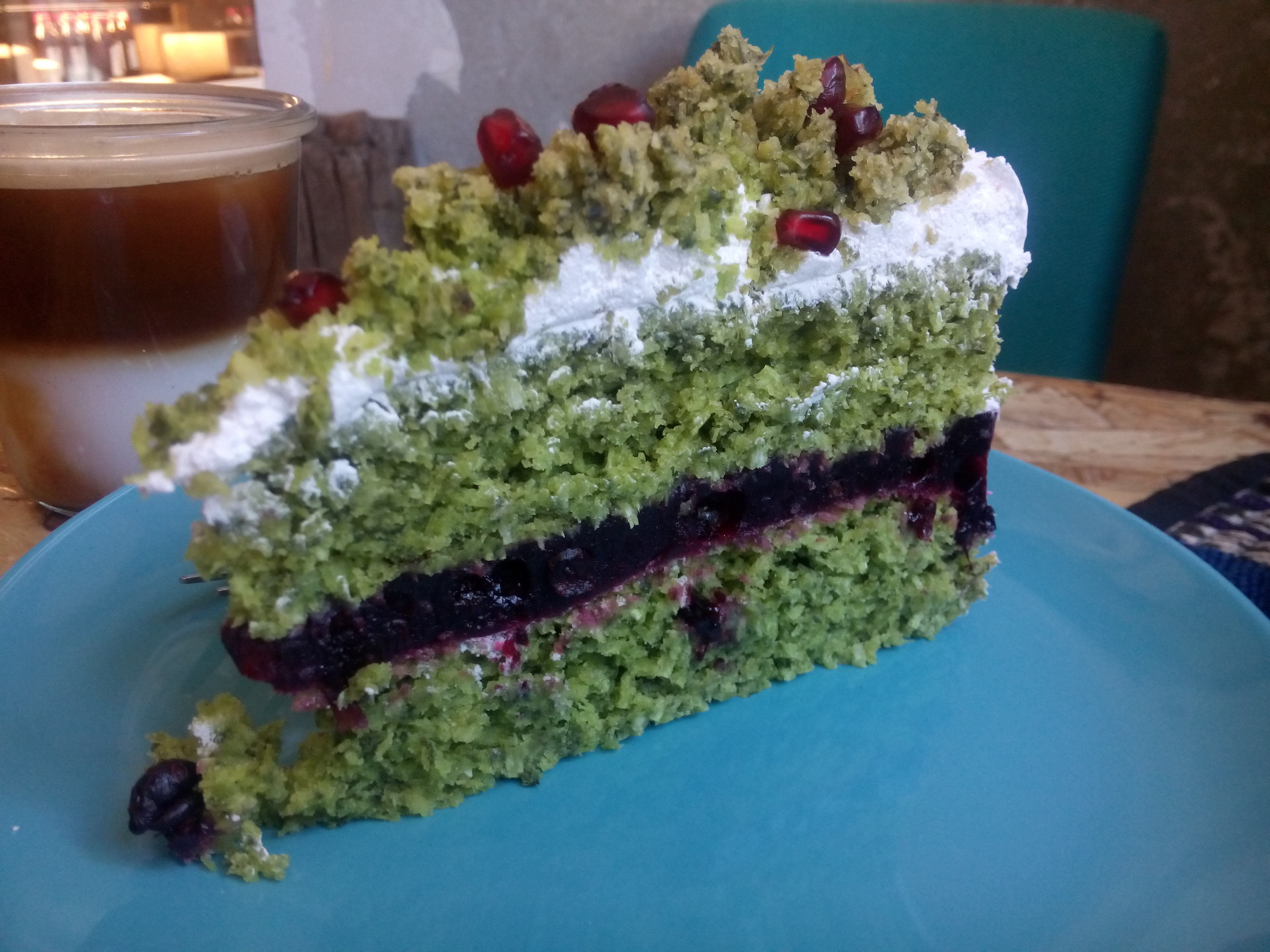 Large wedge of green spongecake with a layer of sour cherry in the middel and coconut cream and pomegranates on top