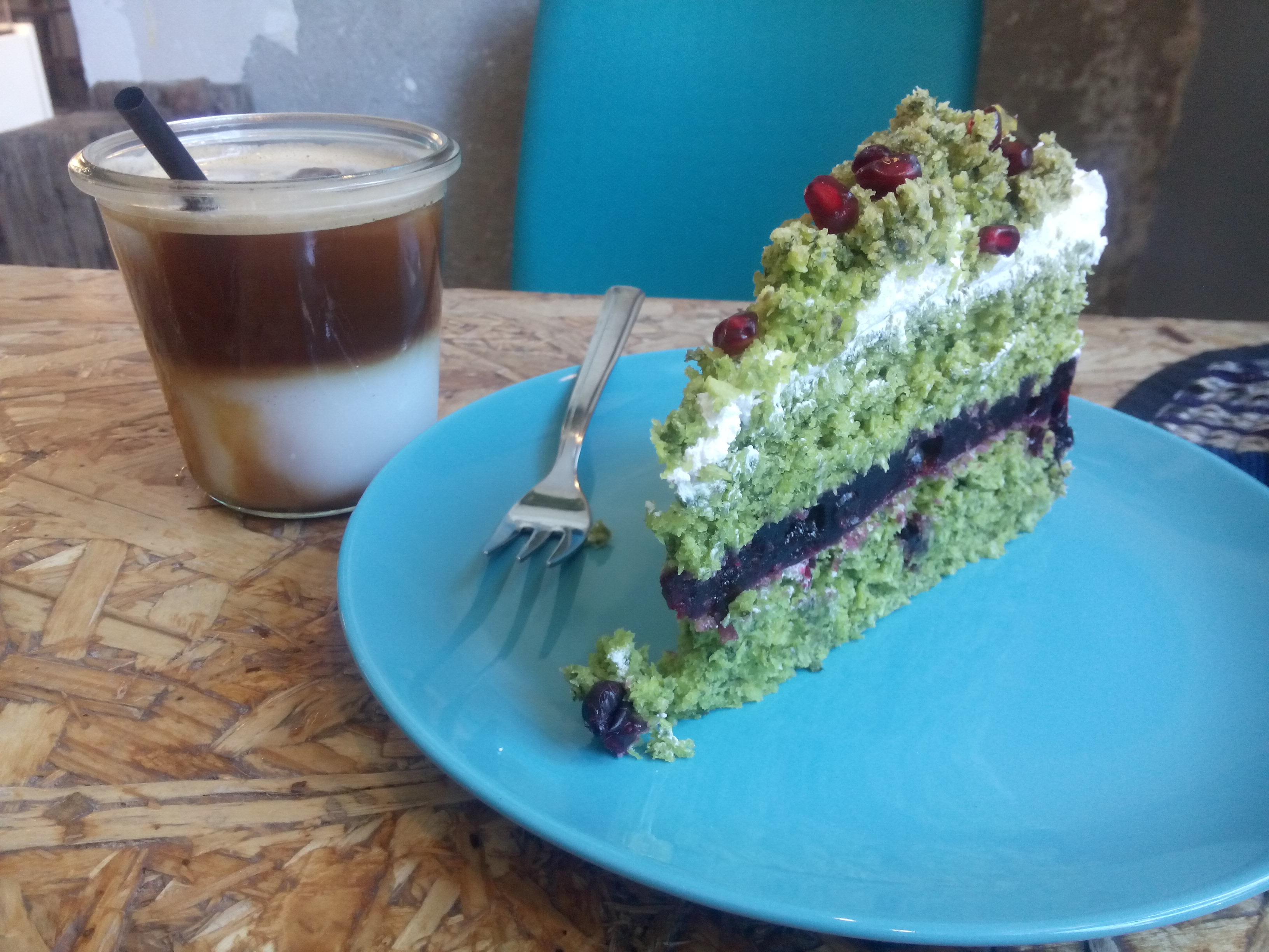A small glass with half white and half brown liquid beside a green cake on a blue plate