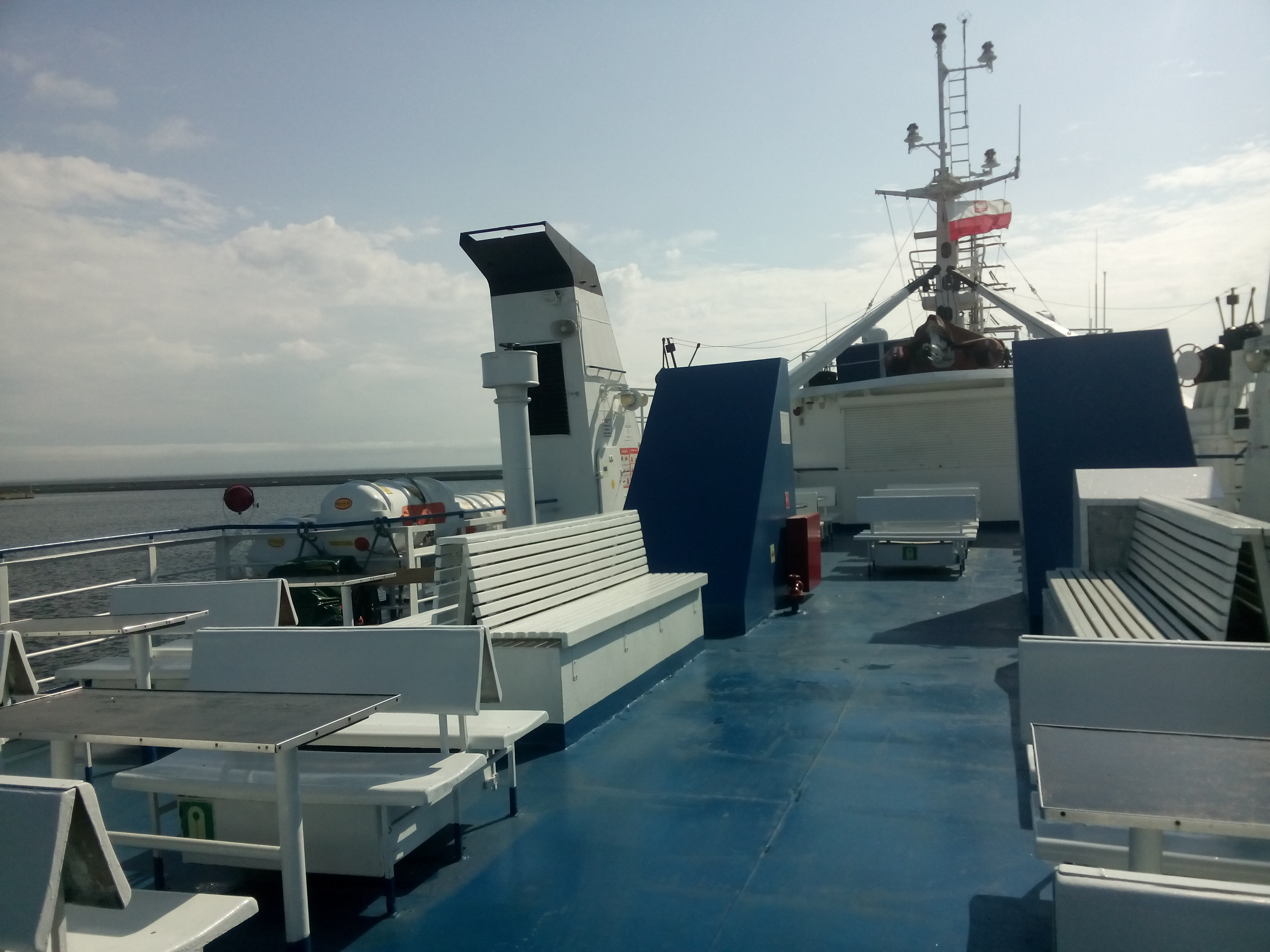 The top deck of a ferry with benches on