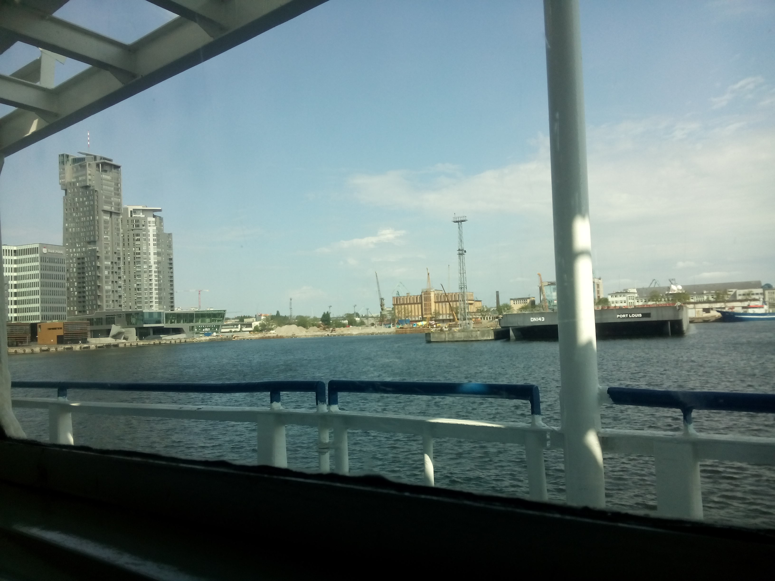 View from inside a ferry across a port to a city