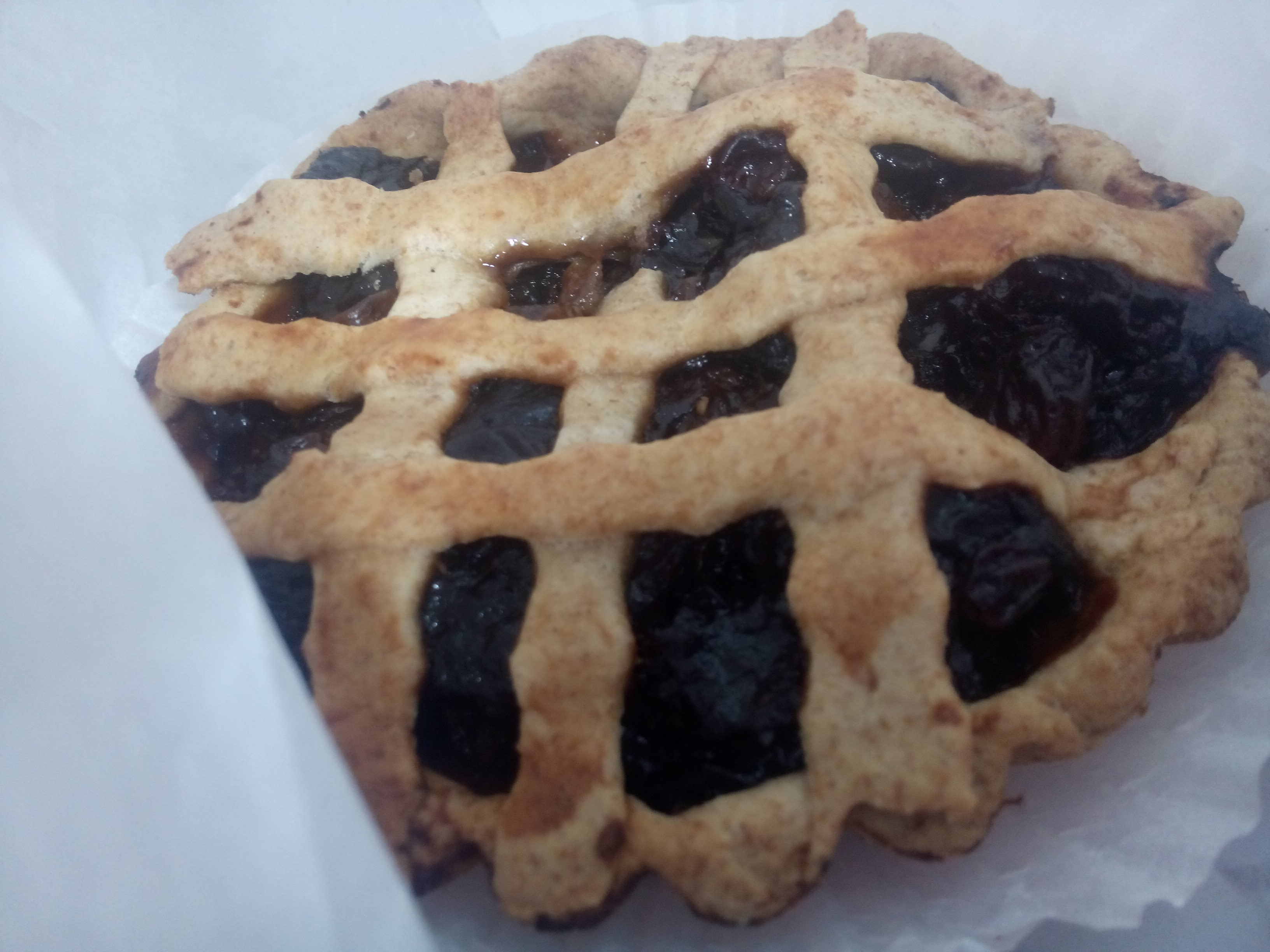 A tart of dark dried fruits criscrossed with pastry in white paper