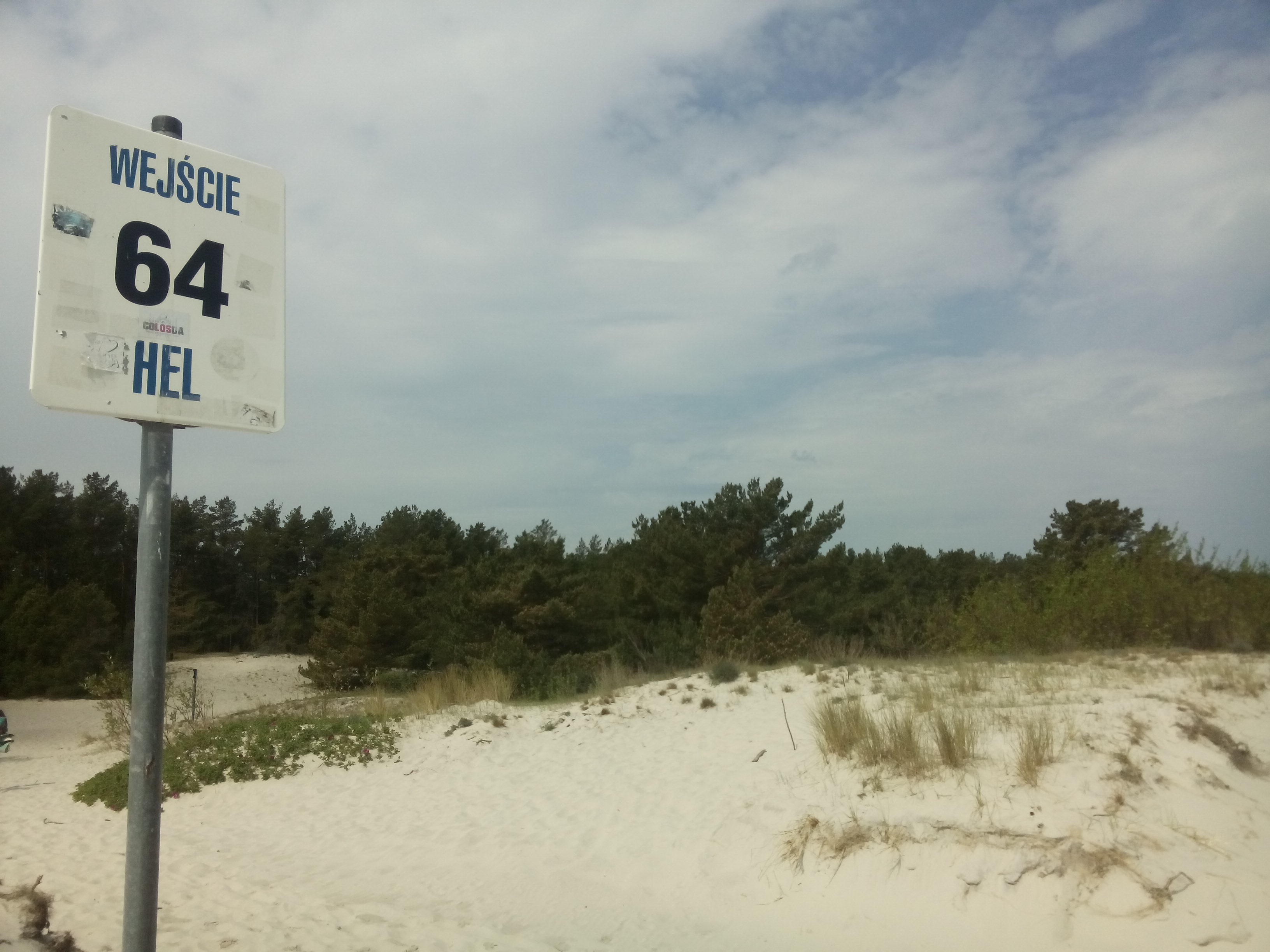 White sand dunes with scattered grass and trees, and a sign saying 64 Hel