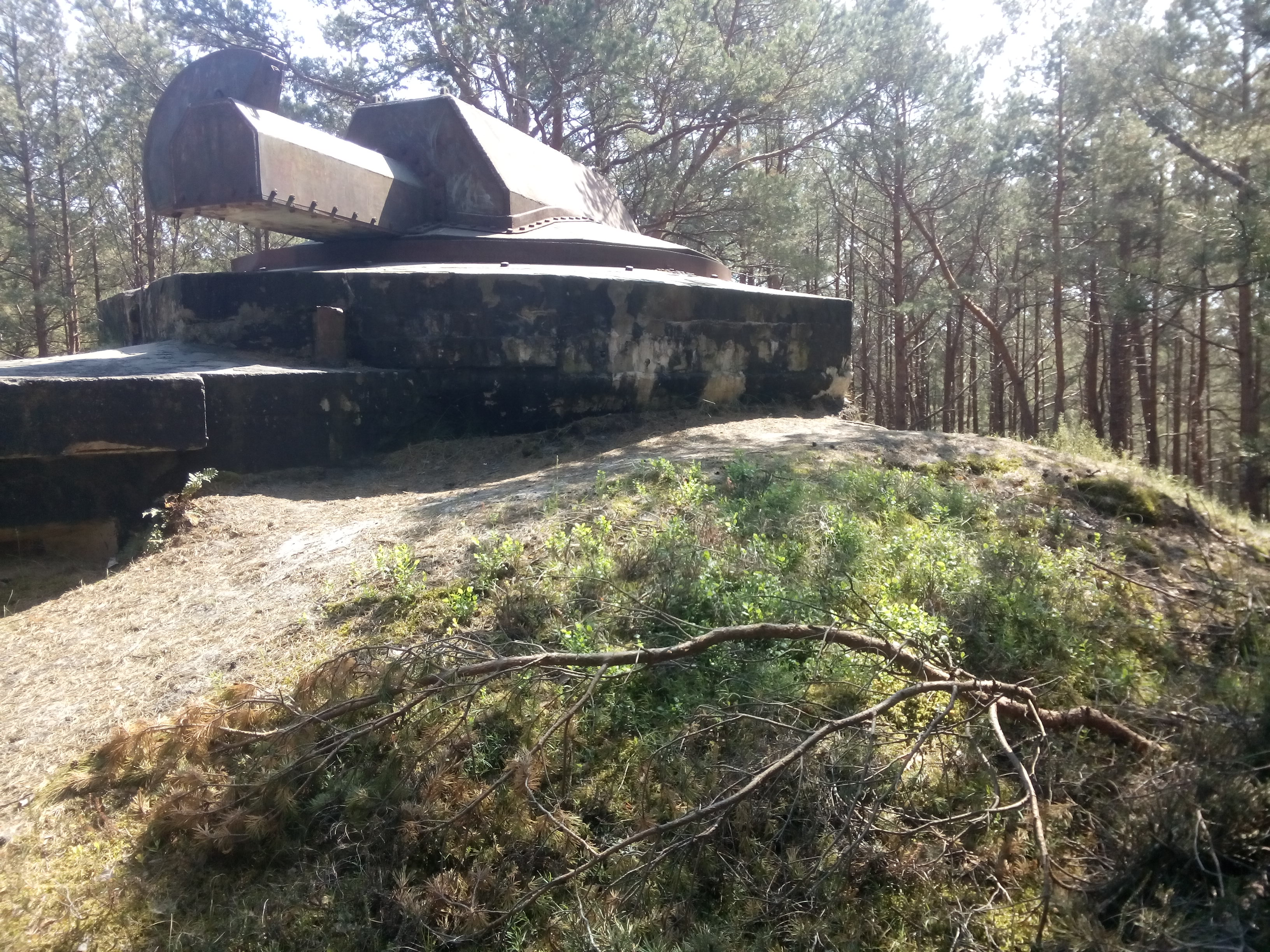 A military shelter that looks like a tank sticking out the top of a dune with grass, and trees in the background