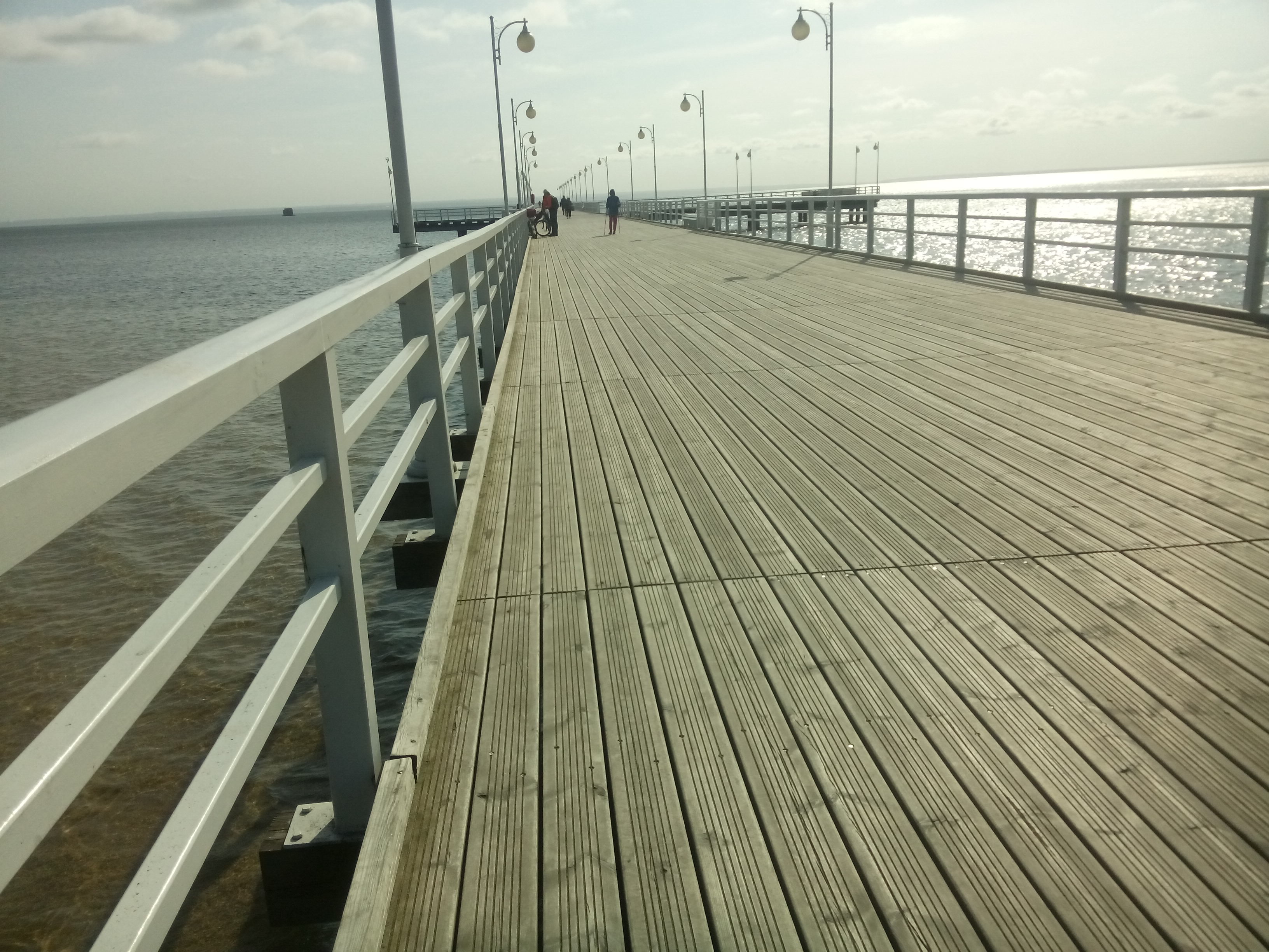 View down a wooden pier with white fences, to the sea