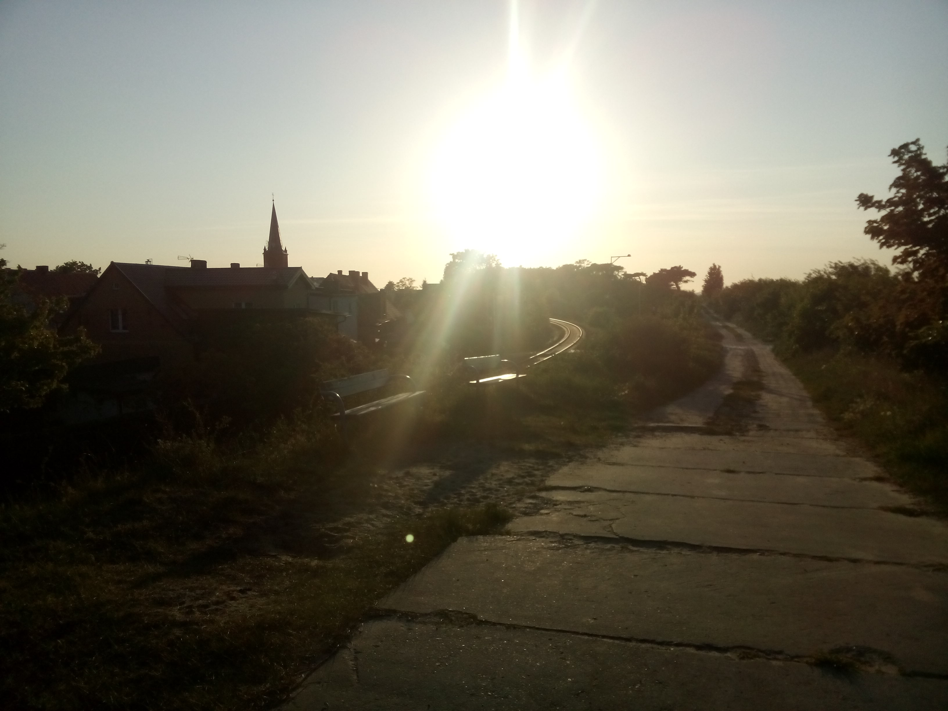 Rough concrete path on the right leading to a sun setting over a town with a church spire