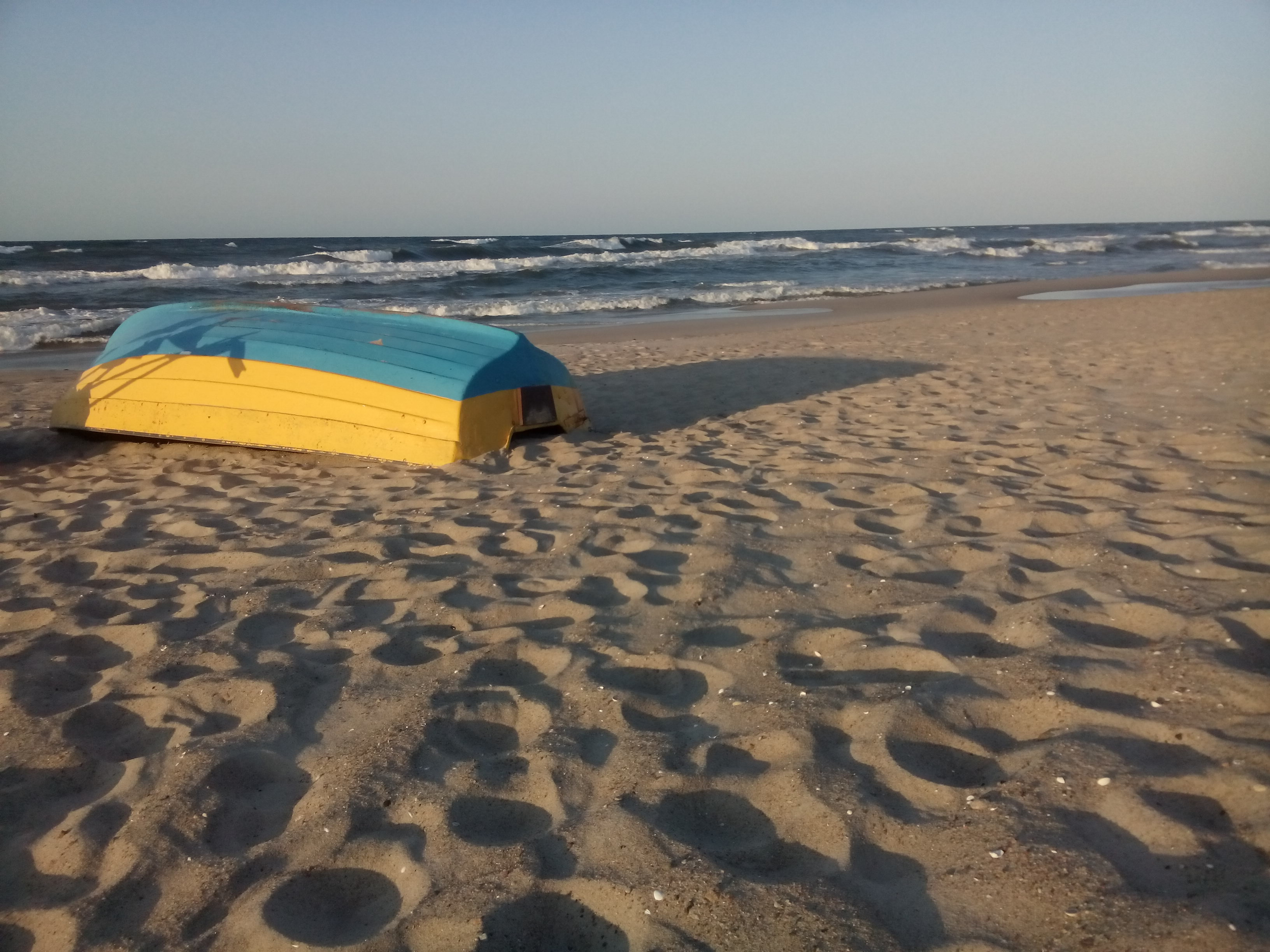 An upturned boat on a beach with rough sea in the background