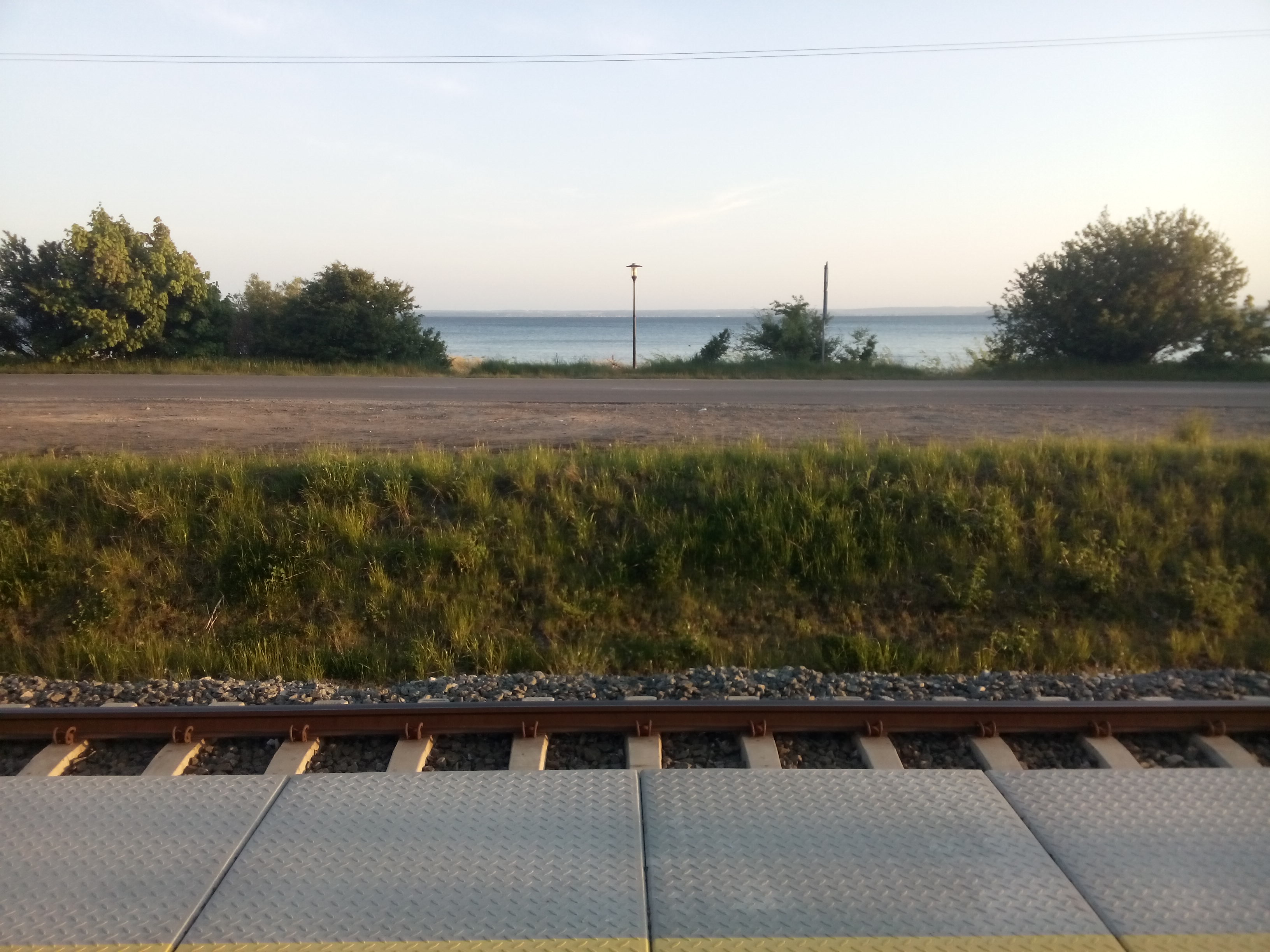 Sea on the horizon with traintracks in the foreground