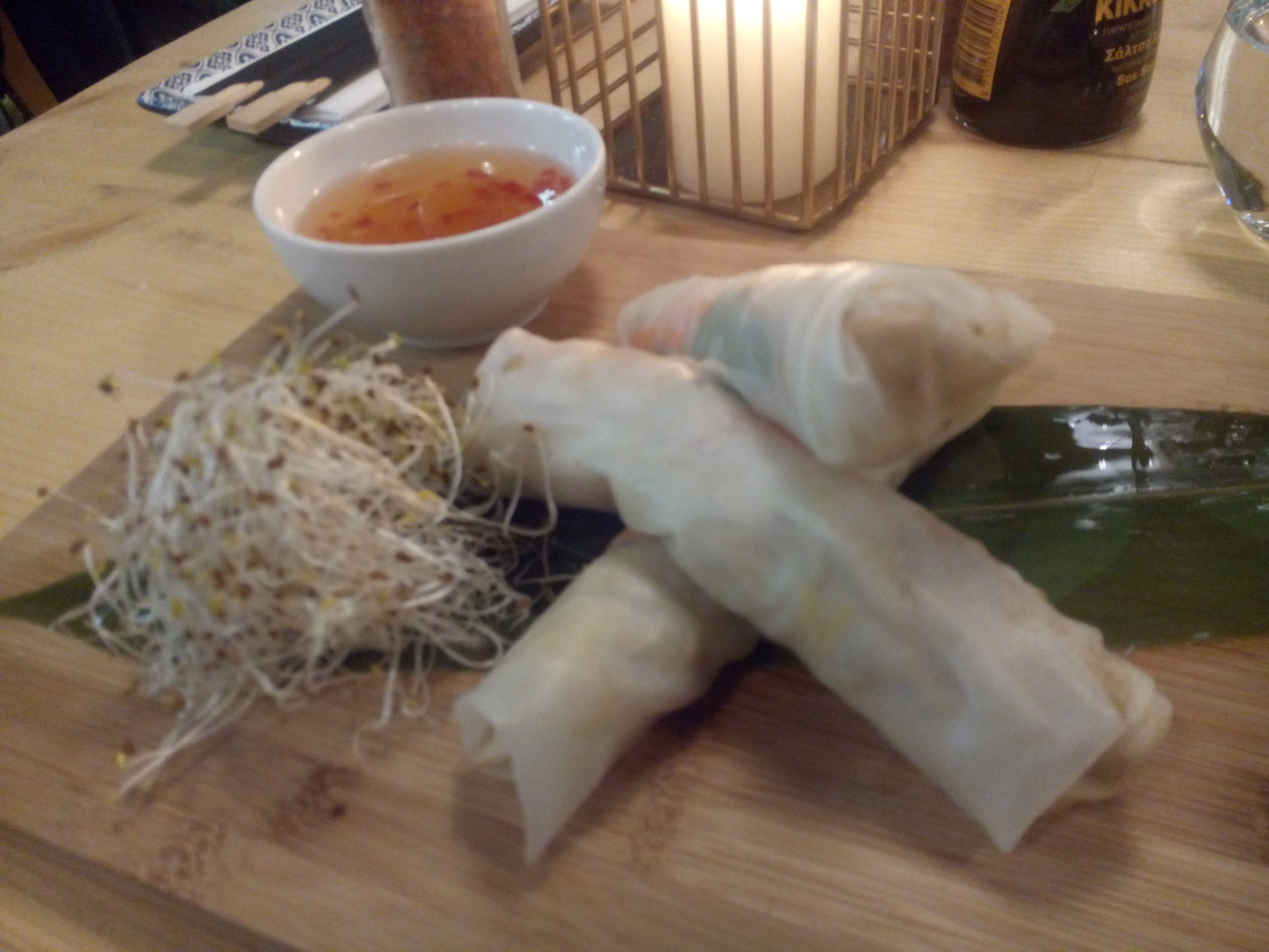 Three large summer rolls stacked on top of each other, beside salad and a bowl of sweet and sour dip