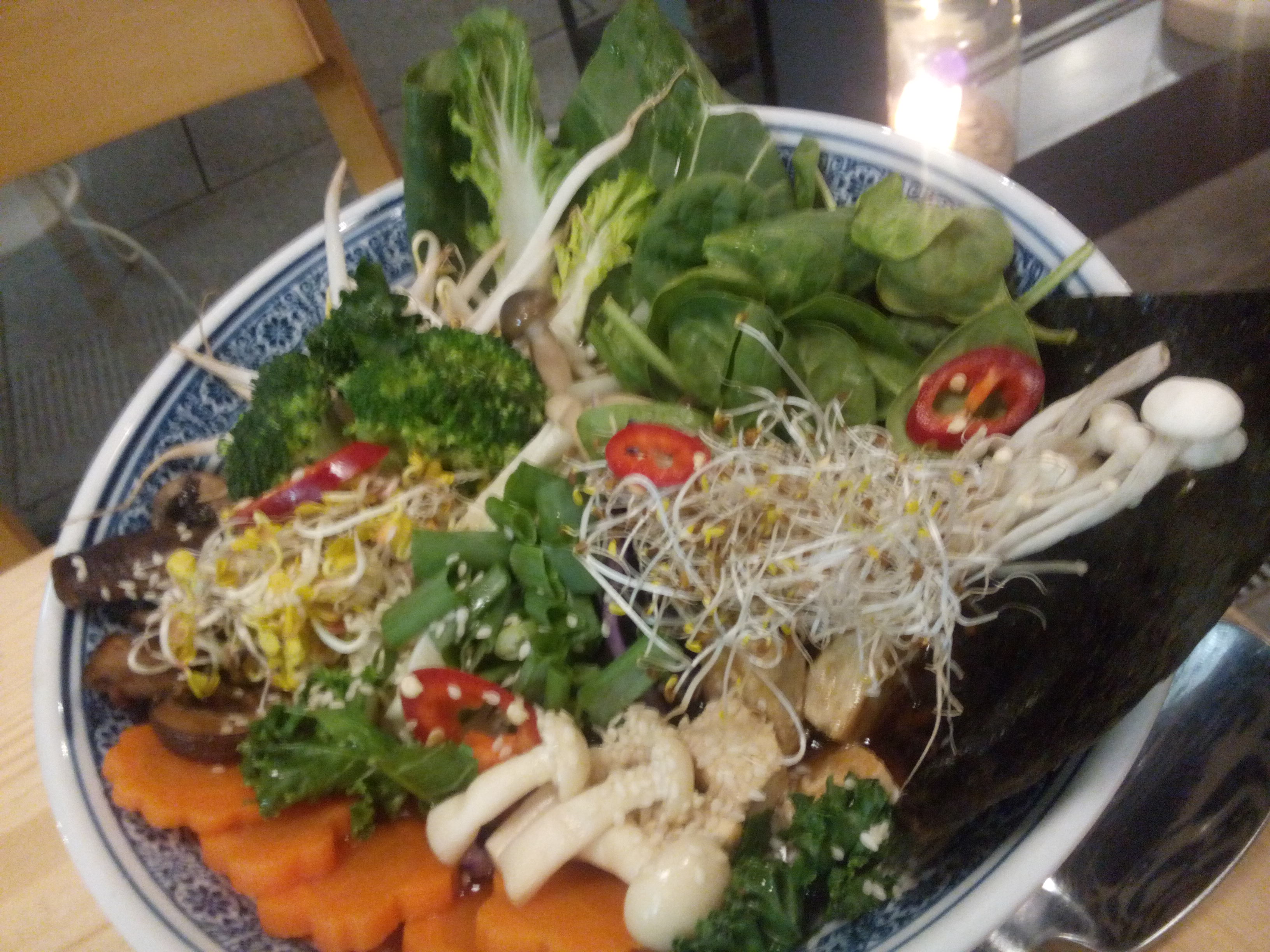 A large bowl exploding with colourful veggies, mushrooms and seaweed