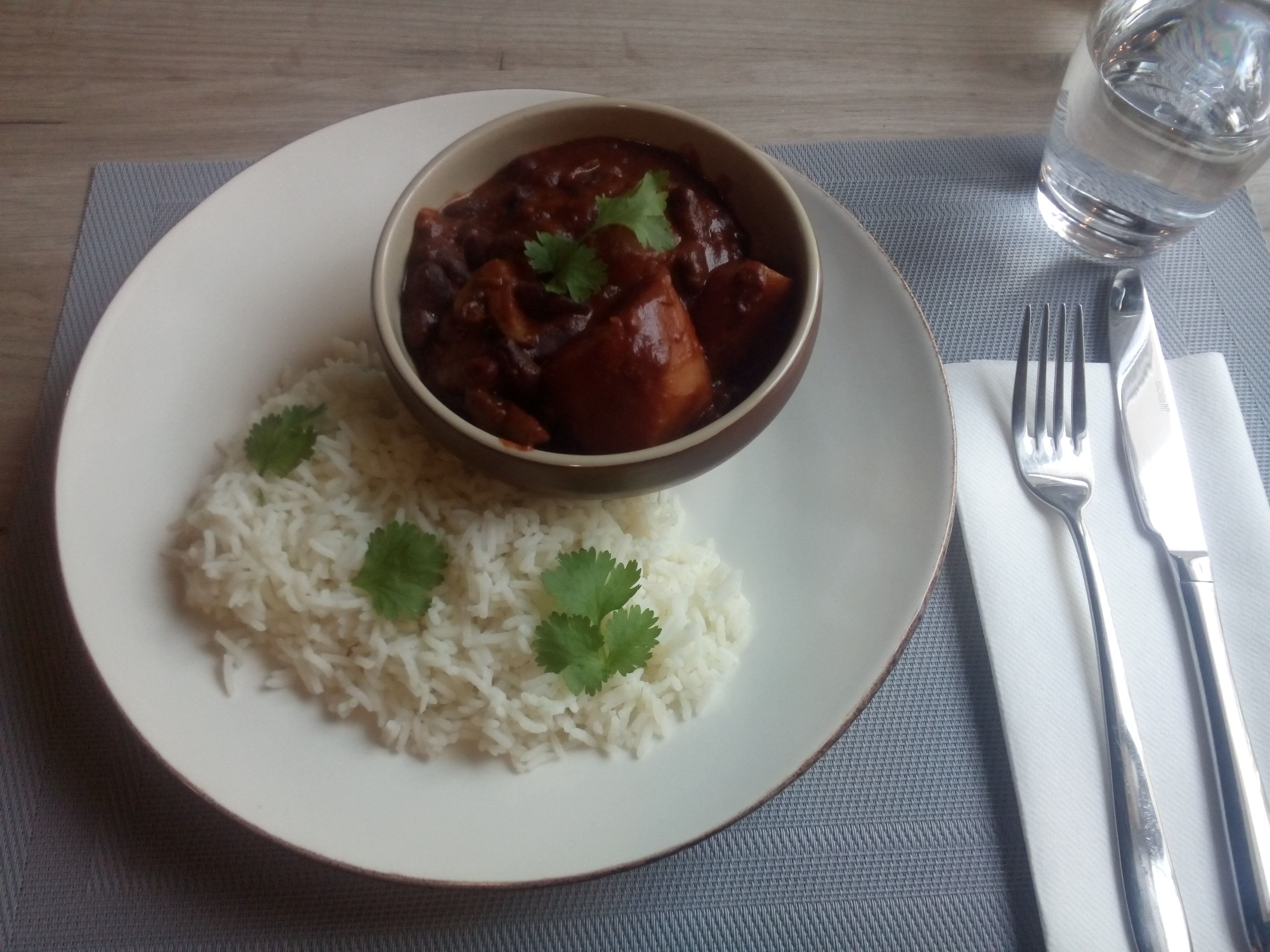 White plate with rice beside a pot of chilli, and a knife and fork and glass of water