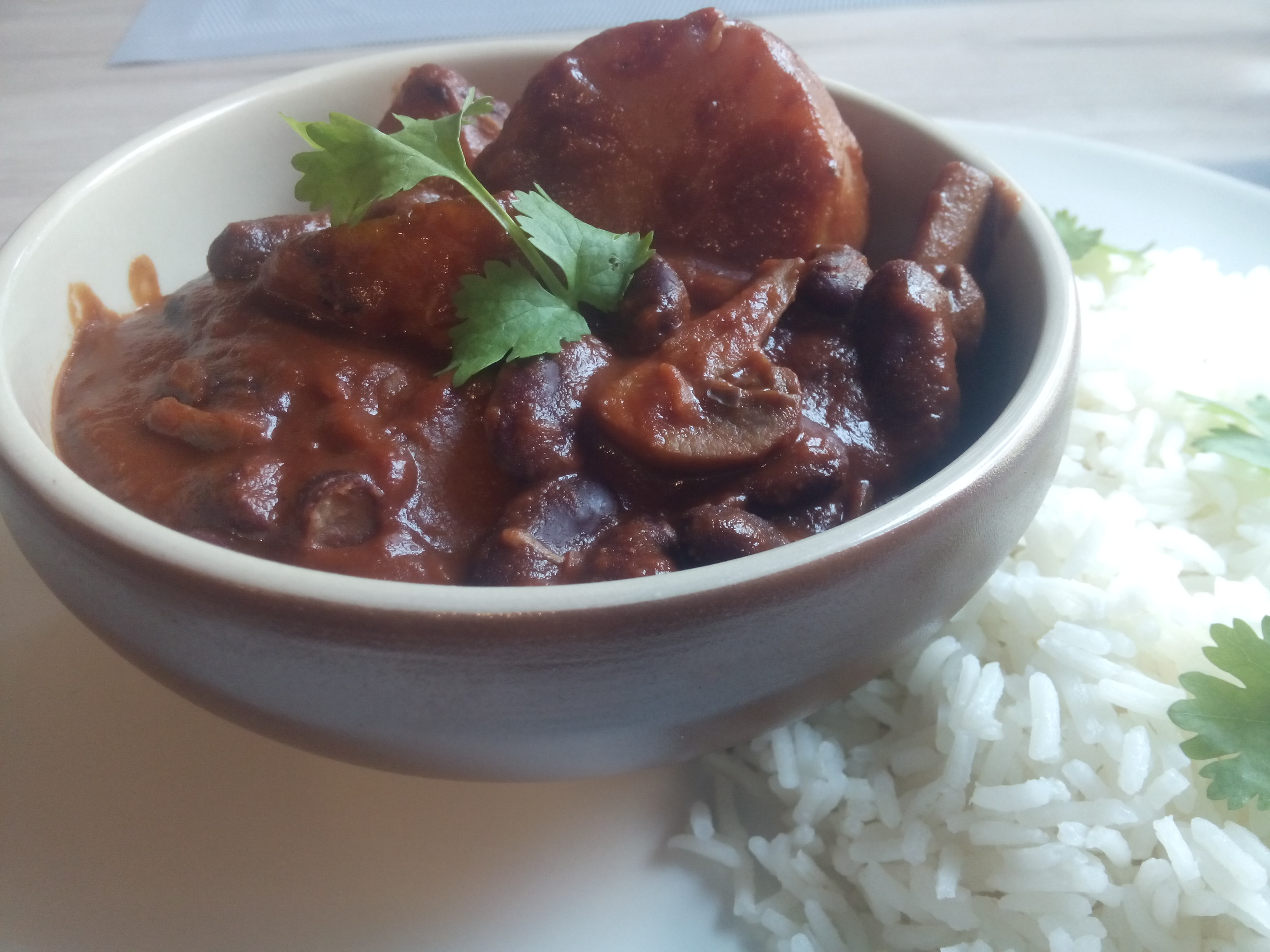 A bowl of beans and vegetables in a chocolate chilli sauce, on a plate beside some rice